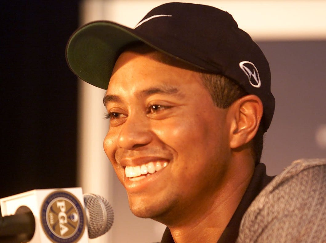 Tiger Woods laughs during press conference.