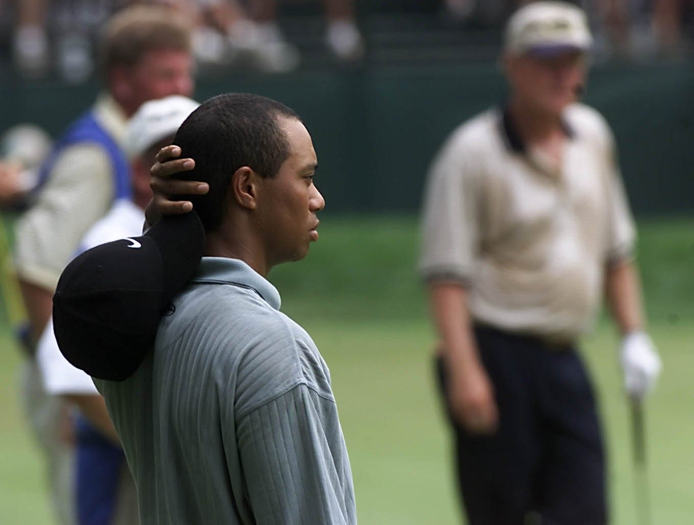 Tiger Woods who shared the early first round lead for the PGA Championship at Valhalla and Jack Nicklaus, background, who struggled through his first round both waited for their chance to putt on the 14th green.
