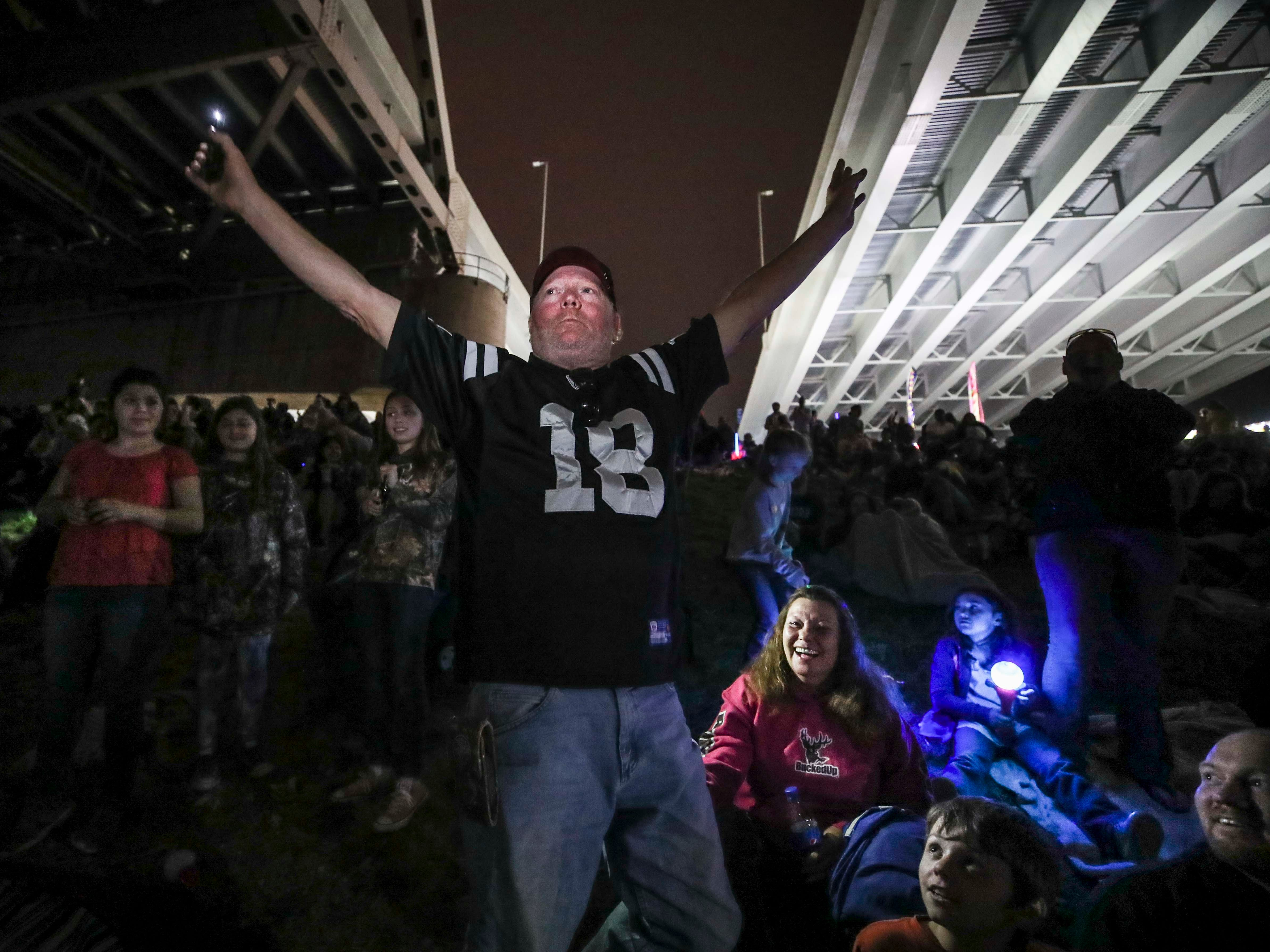 Tom Mulvaney of Lexington, Ind. yells to the crowd to light up their phones before the fireworks in Jeffersonville during 2019 Thunder Over Louisville. 'Let's show Kentucky what Hoosiers got,' he yelled to a roar from the crowd. April 13, 2019