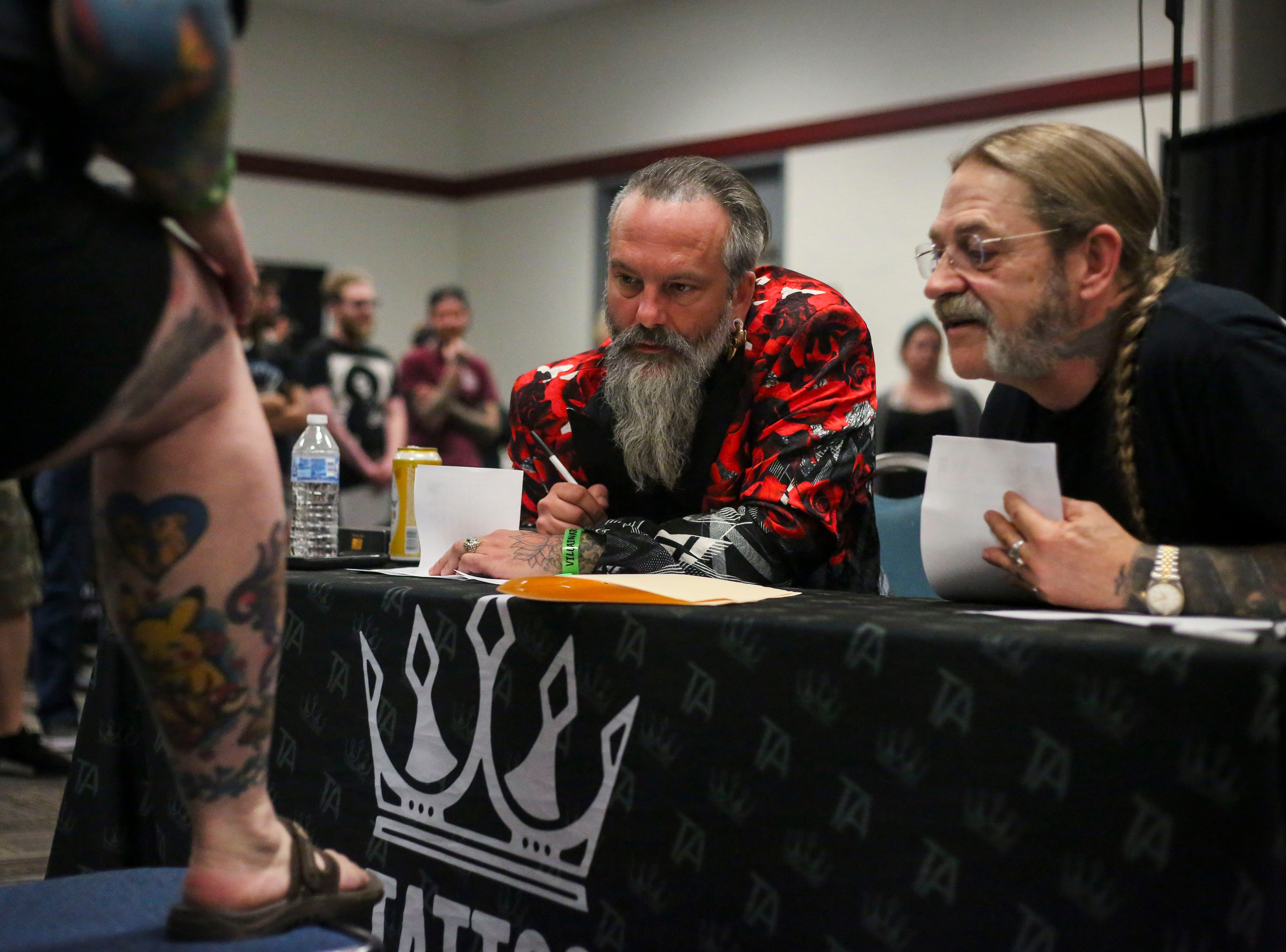 Troy Timpel, Villain Arts, middle, judges Christian Warnest's, left,  tattoo on her shin during the tattoo contest at the 8th Annual Louisville Tattoo Arts Convention put on by Villain Arts at the Kentucky Expo Center in Louisville, Ky. on Saturday, April 13, 2019.