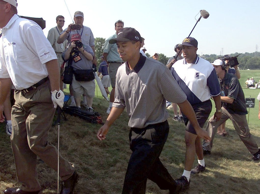 Tiger Woods walks with security to the clubhouse from the practice tee.