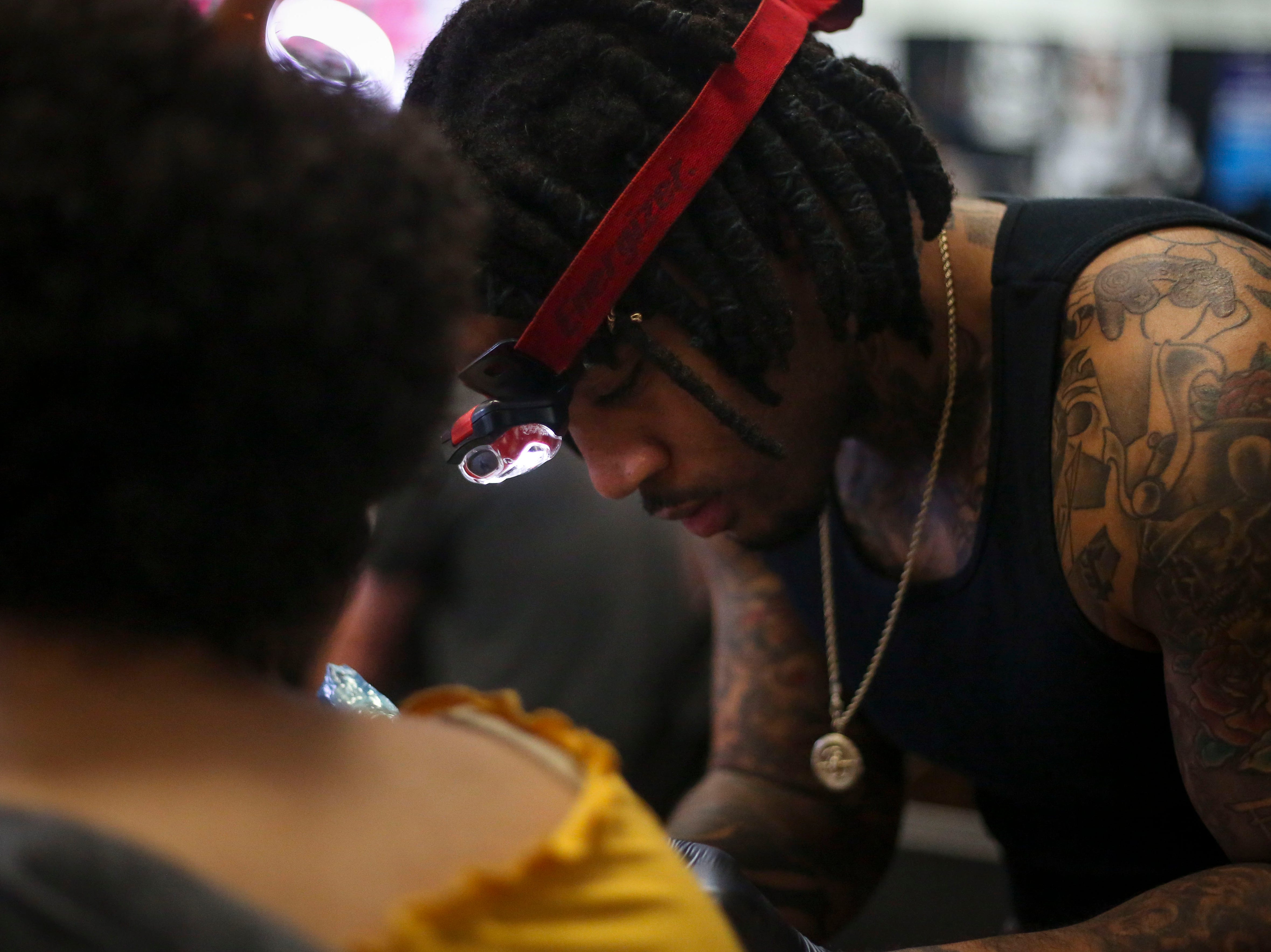 Dexter Banks tattoos Kelly Bradford during the 8th Annual Louisville Tattoo Arts Convention put on by Villain Arts at the Kentucky Expo Center in Louisville, Ky. on Saturday, April 13, 2019.