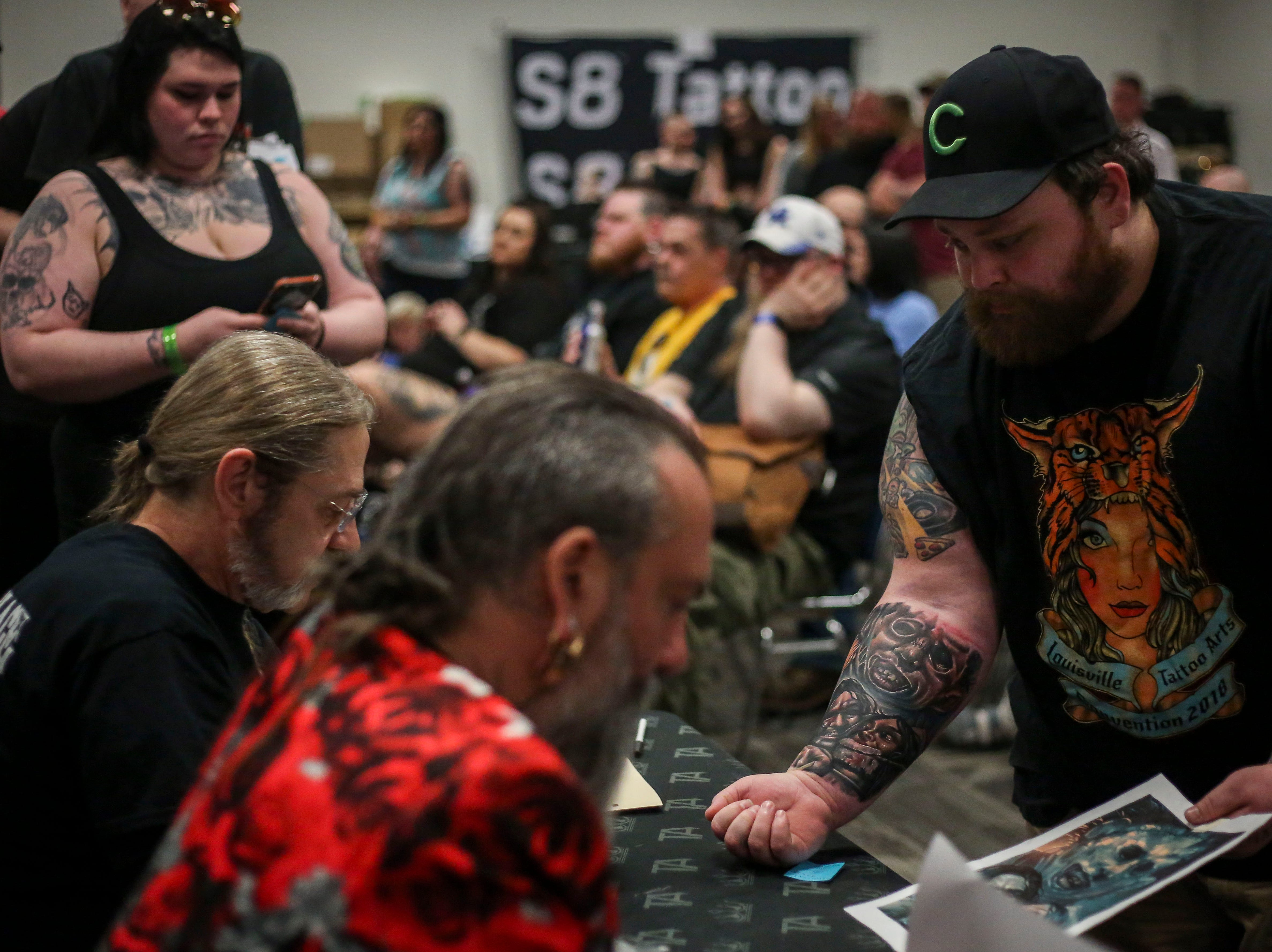 Adam Farmer shows off his arm piece to the judges during the tattoo contest at the 8th Annual Louisville Tattoo Arts Convention put on by Villain Arts at the Kentucky Expo Center in Louisville, Ky. on Saturday, April 13, 2019.