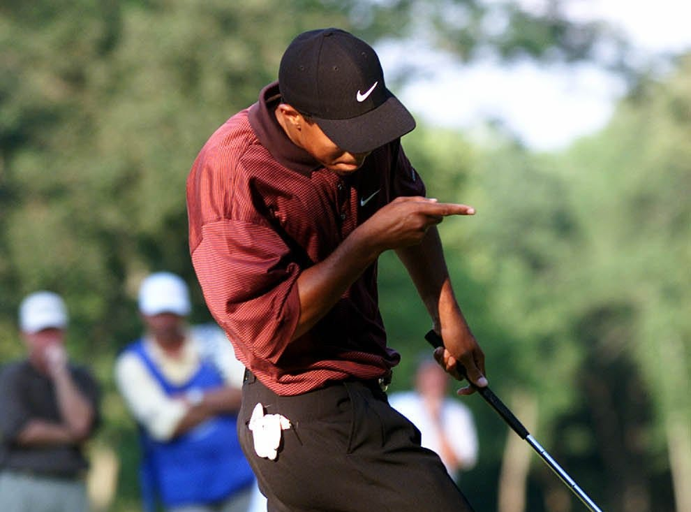 Tiger Woods coaxes the ball into the hole on the sixteenth green during the playoff at Valhalla.-