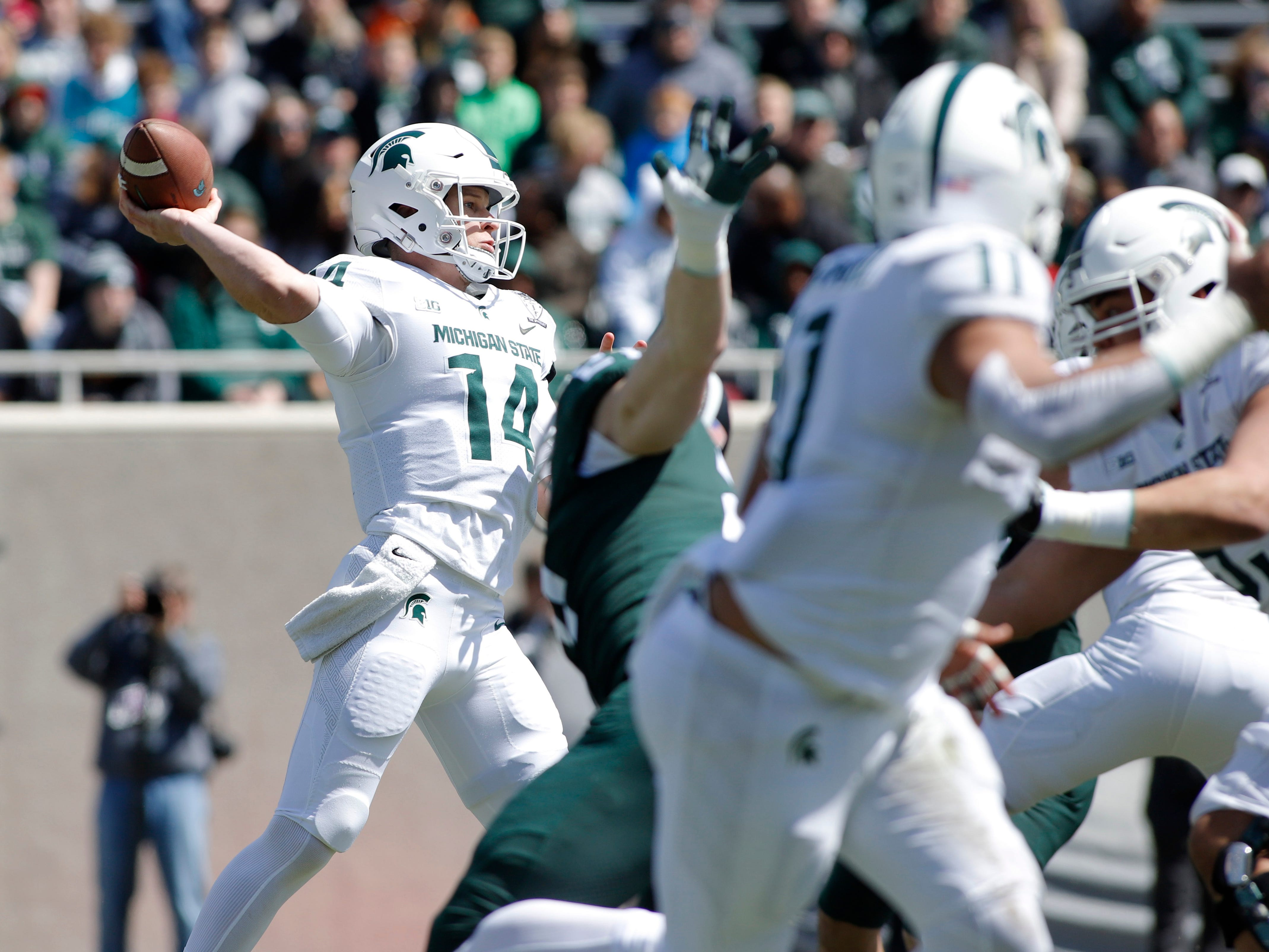 Michigan State quarterback Brian Lewerke, left, throws a pass during an NCAA college football spring scrimmage game, Saturday, April 13, 2019, in East Lansing, Mich. (AP Photo/Al Goldis)