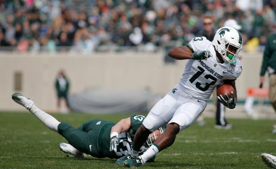 Michigan State's Laress Nelson, right, eludes a tackle attempt by Jack Mandryk during an NCAA college football spring scrimmage game, Saturday, April 13, 2019, in East Lansing, Mich. (AP Photo/Al Goldis)
