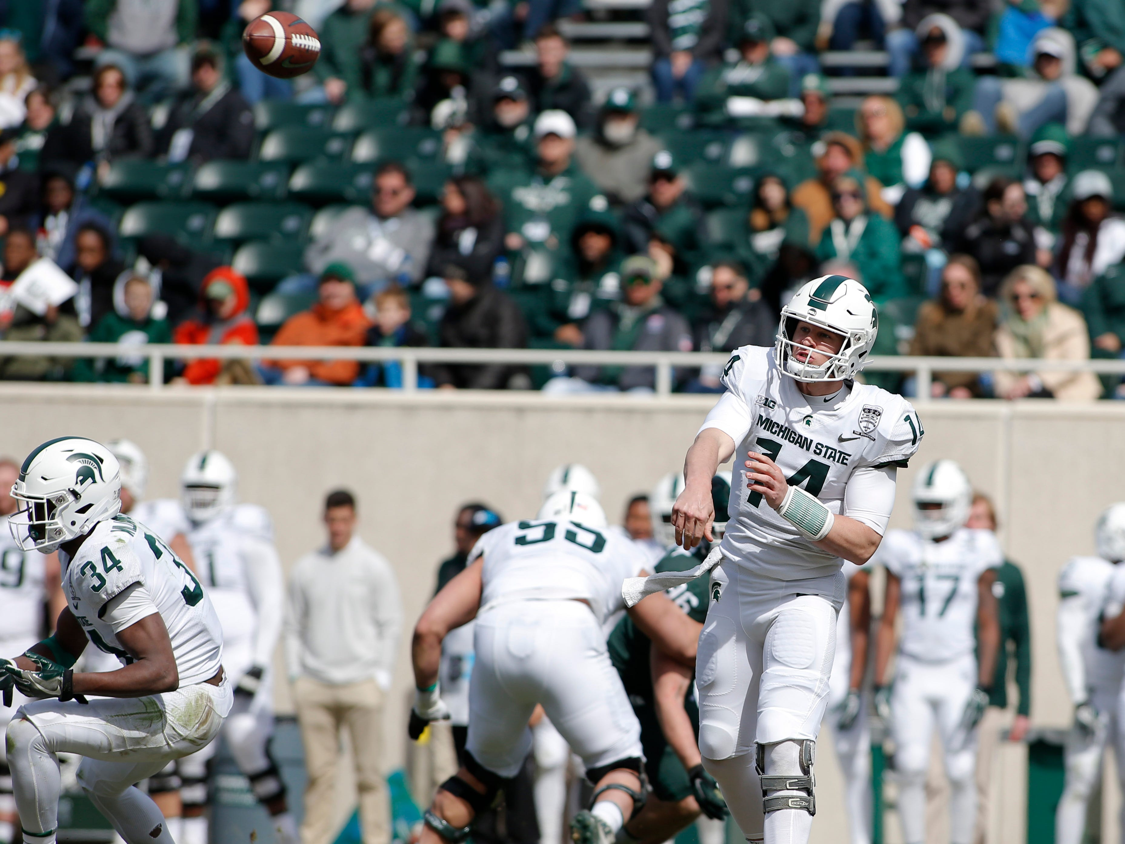 Michigan State quarterback Brian Lewerke, right, throws a pass as Anthony Williams (34) blocks during an NCAA college football spring scrimmage game, Saturday, April 13, 2019, in East Lansing, Mich. (AP Photo/Al Goldis)