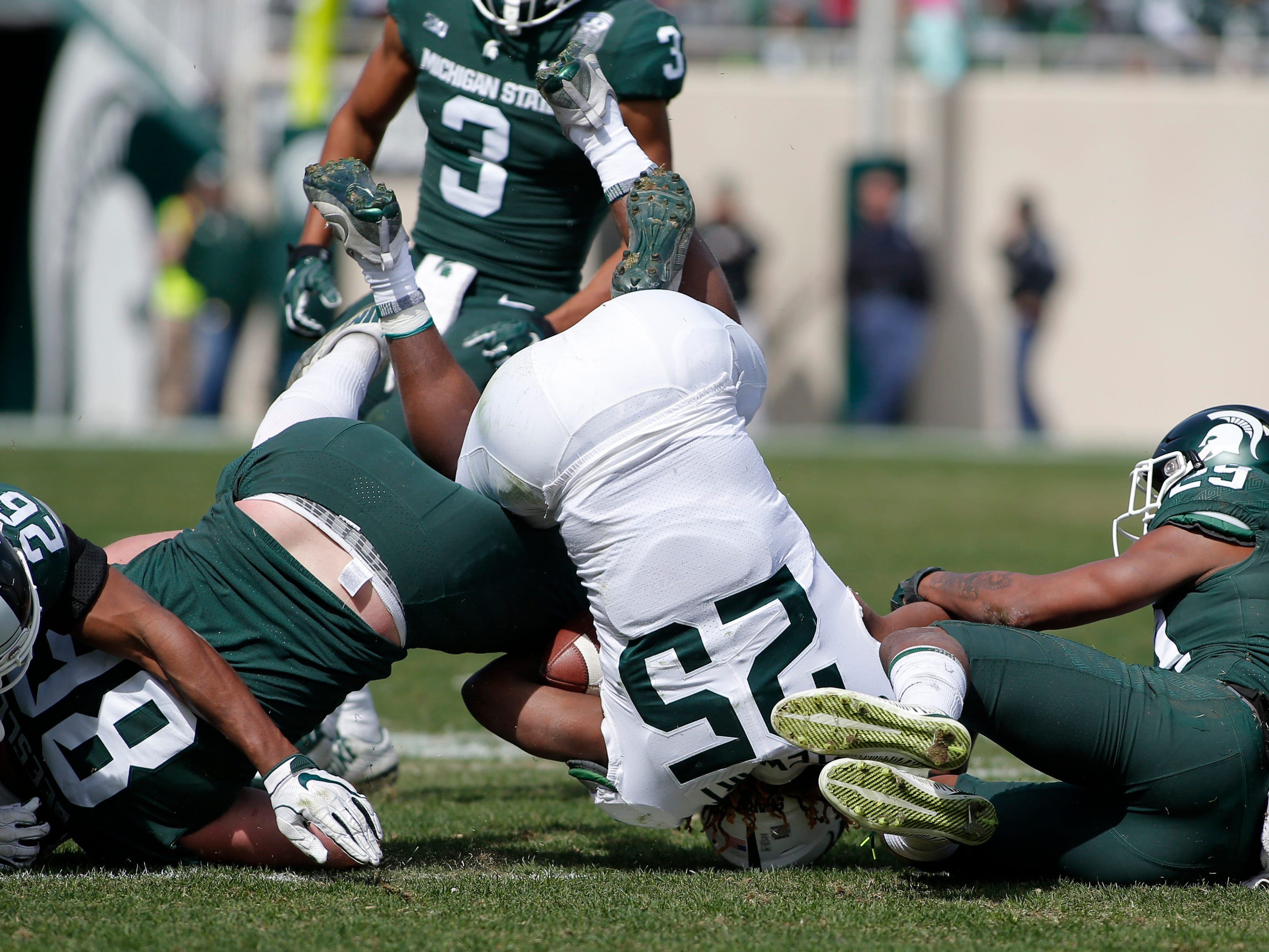 Michigan State's Darrell Stewart Jr. (25) is upended by Shakur Brown, right, Brandon Bouyer-Randle (26) and Drew Beesley during an NCAA college football spring scrimmage game, Saturday, April 13, 2019, in East Lansing, Mich. (AP Photo/Al Goldis)