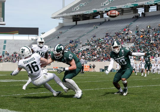 Michigan State's Brandon Sowards (16), Jack Mandryk (43) and Kalon Gervin, right, vie for a deflected pass intended for Sowards during an NCAA college football spring scrimmage game, Saturday, April 13, 2019, in East Lansing, Mich. The pass fell incomplete. (AP Photo/Al Goldis)