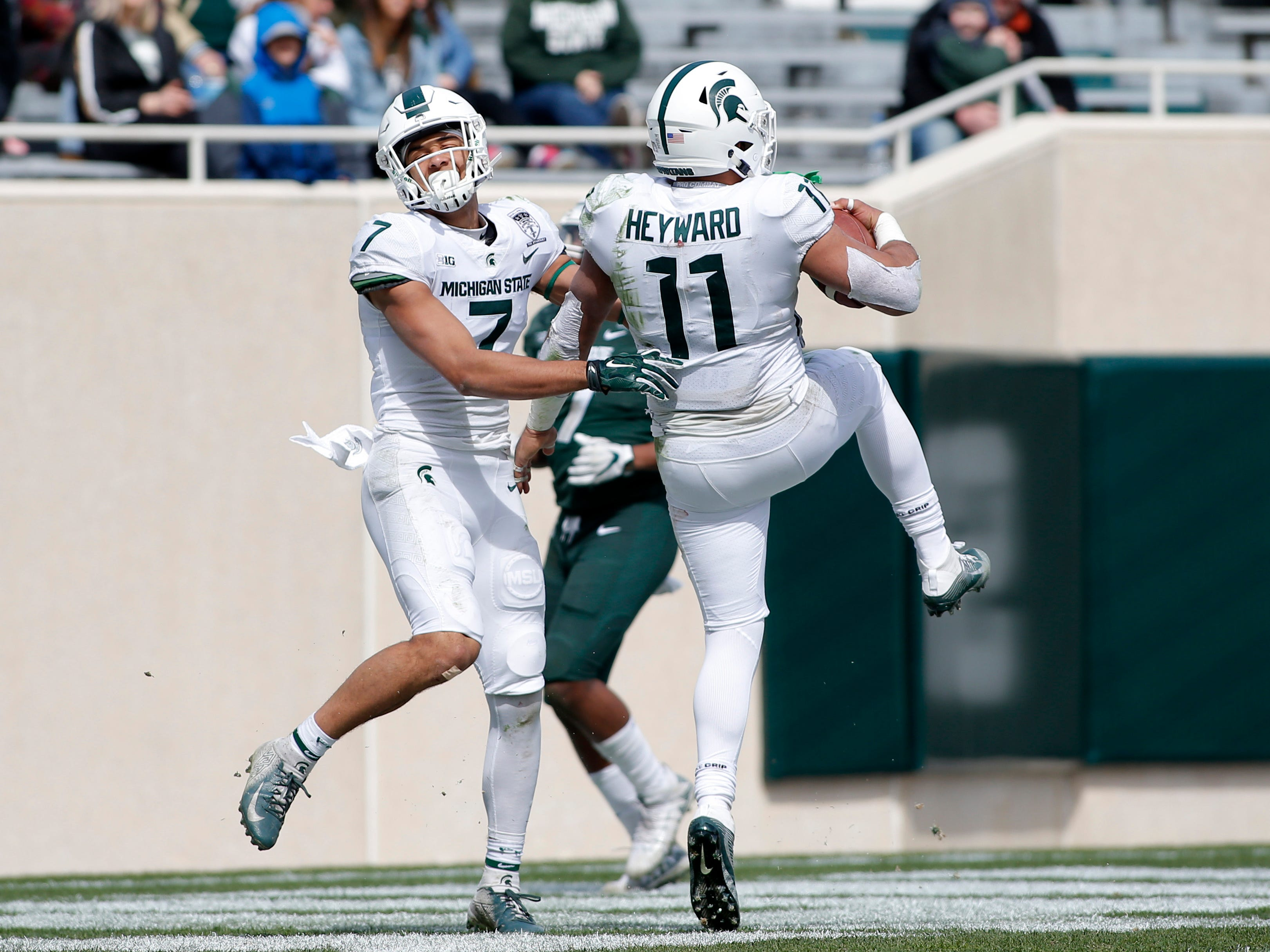 Michigan State's Connor Heyward, right, and Cody White (7) celebrate Heyward's touchdown during an NCAA college football spring scrimmage game, Saturday, April 13, 2019, in East Lansing, Mich. (AP Photo/Al Goldis)