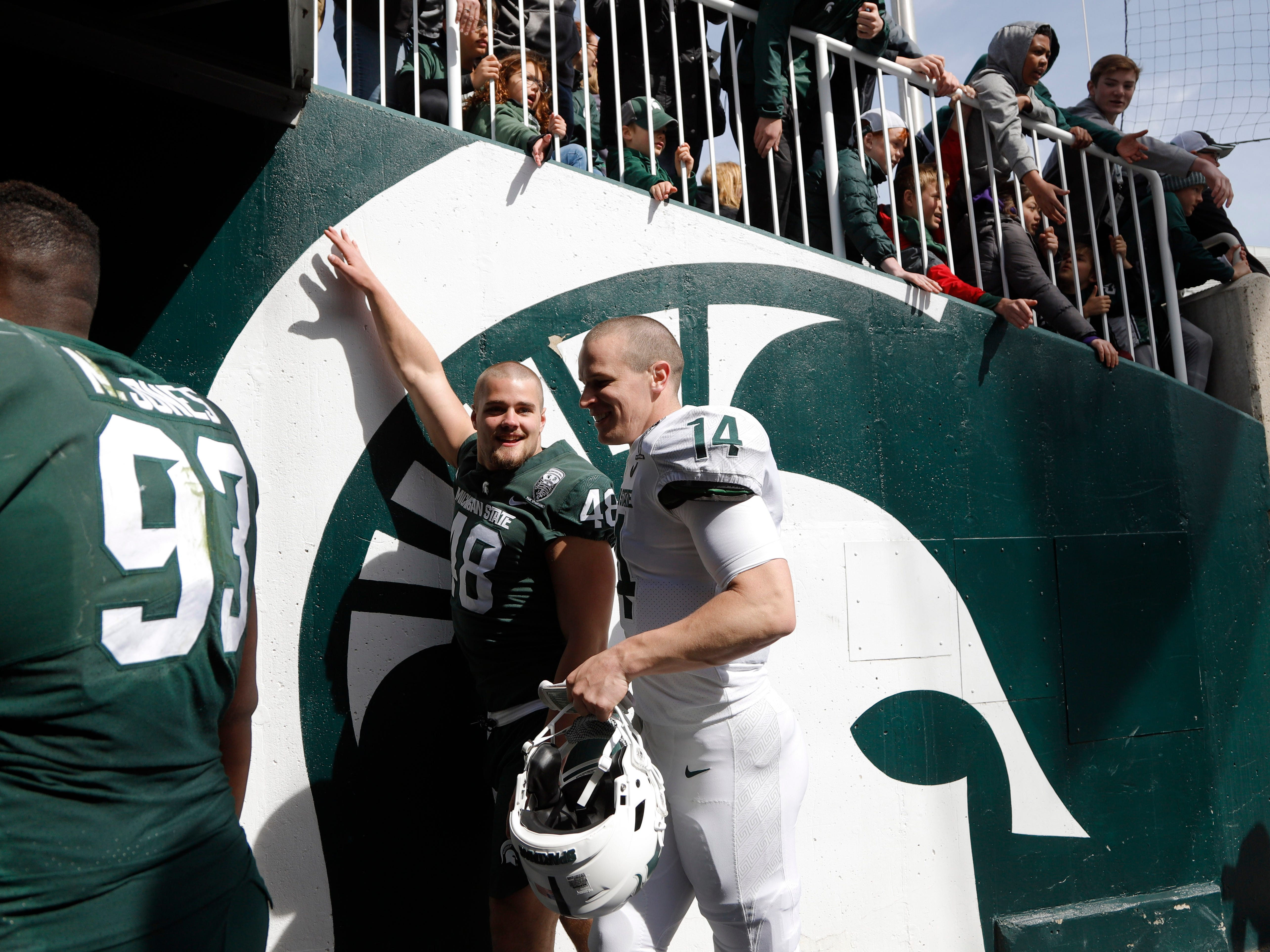 Michigan State quarterback Brian Lewerke, right, and defensive end Kenny Willekes (48) leave the field after an NCAA college football spring scrimmage game, Saturday, April 13, 2019, in East Lansing, Mich. (AP Photo/Al Goldis)