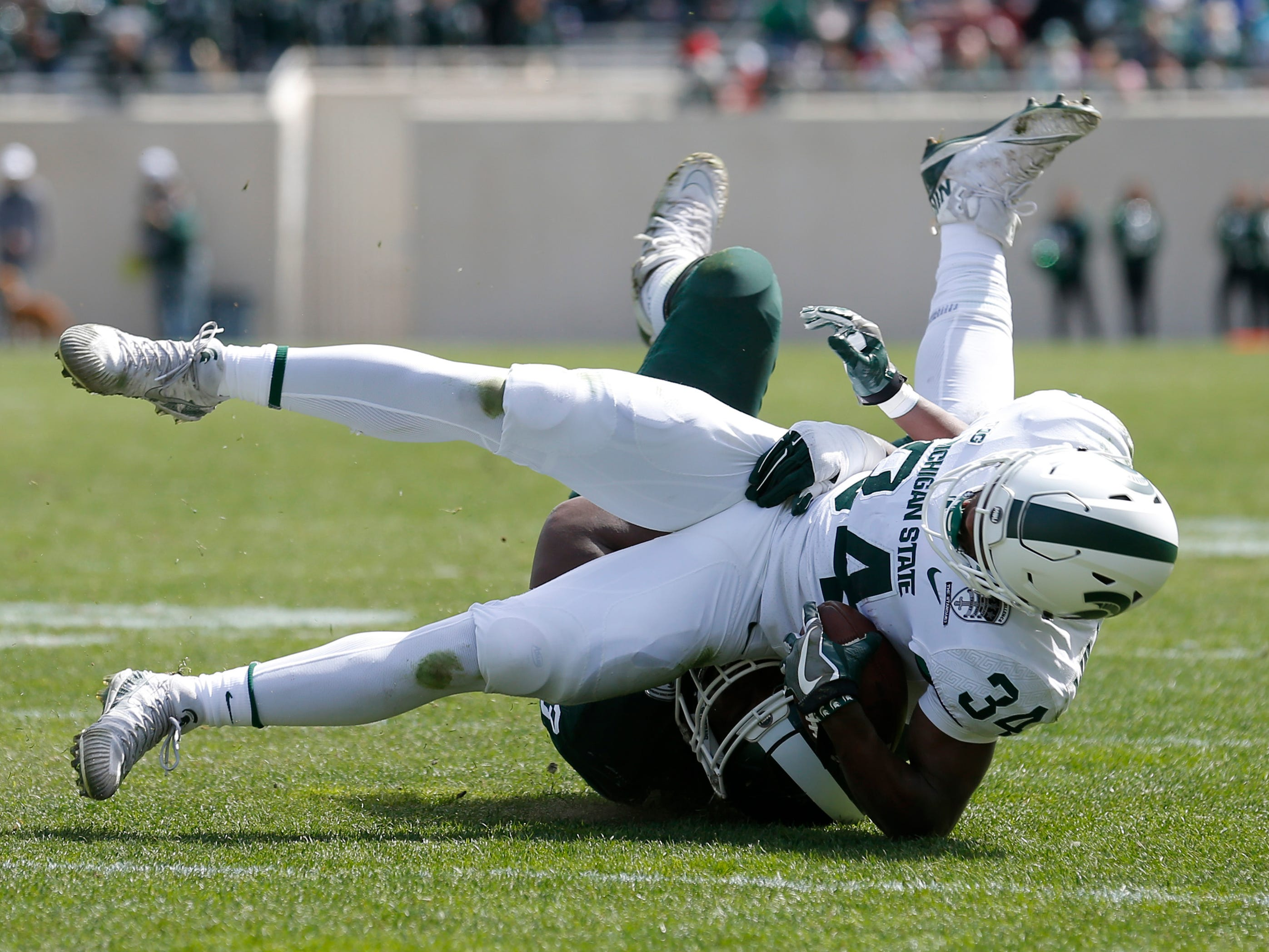 Michigan State's Anthony Williams (34) is tackled by Naquan Jones during an NCAA college football spring scrimmage game, Saturday, April 13, 2019, in East Lansing, Mich. (AP Photo/Al Goldis)