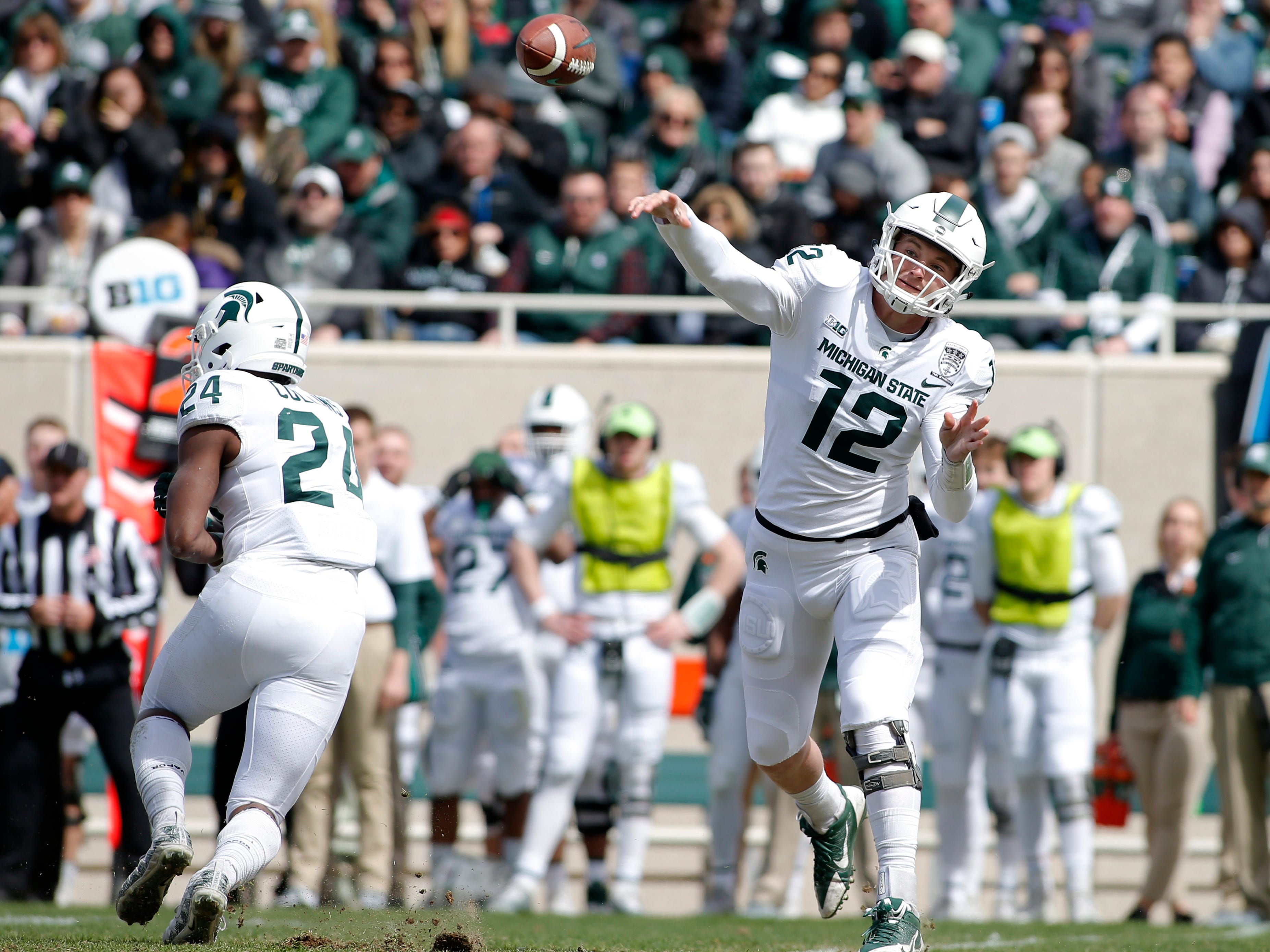 Michigan State quarterback Rocky Lombardi, right, throws a pass as Elijah Collins (24) blocks during an NCAA college football spring scrimmage game, Saturday, April 13, 2019, in East Lansing, Mich. (AP Photo/Al Goldis)