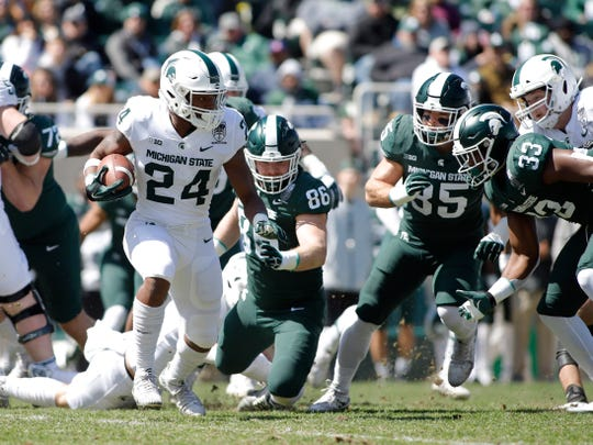 Michigan State's Elijah Collins, left, rushes against Jonathan Brys (86), Jeslord Boateng (33) and Joe Bachie during an NCAA college football spring scrimmage game, Saturday, April 13, 2019, in East Lansing, Mich. (AP Photo/Al Goldis)