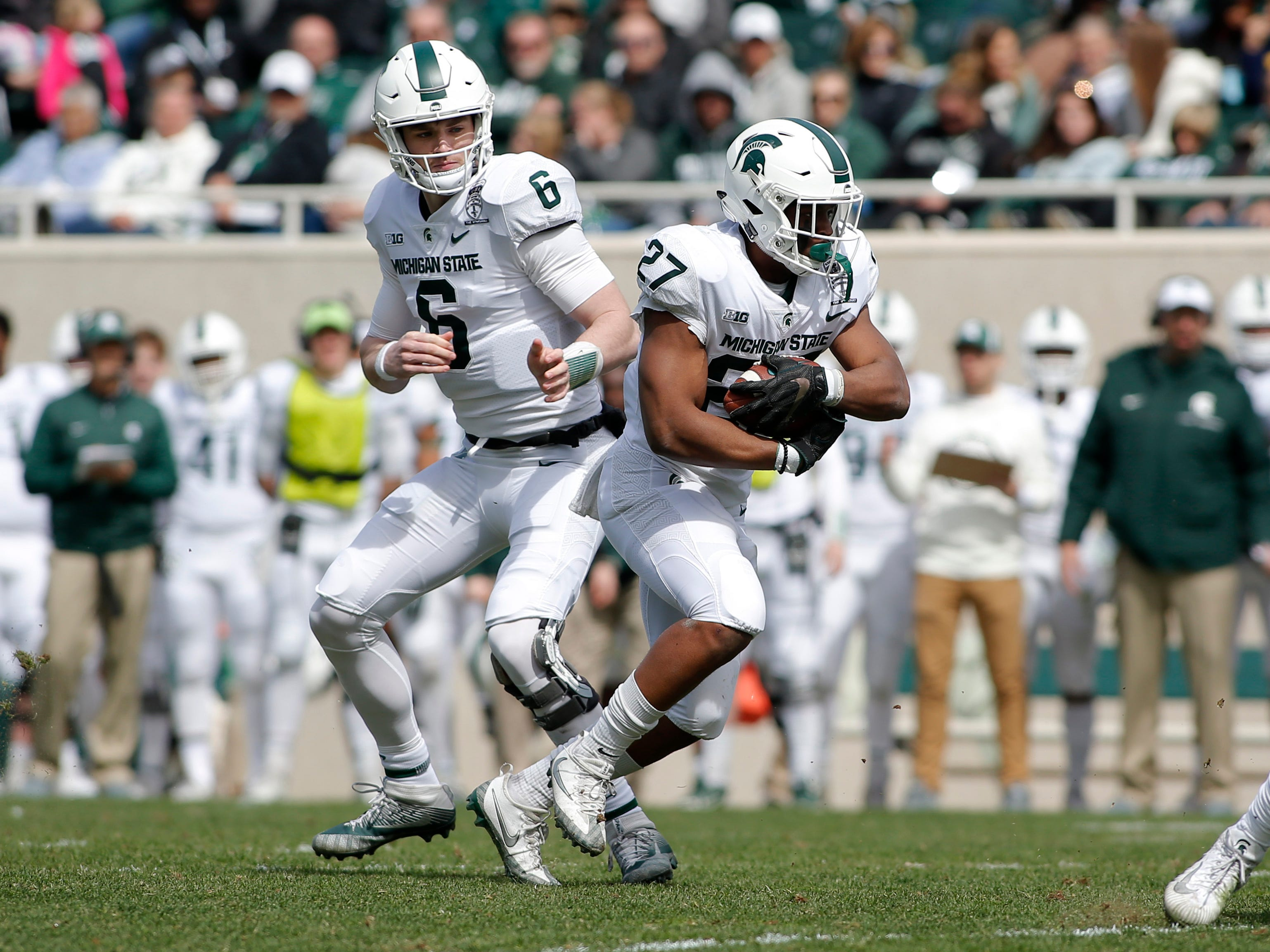 Michigan State running back Weston Bridges, right, takes a handoff from quarterback Theo Day (6) during an NCAA college football spring scrimmage game, Saturday, April 13, 2019, in East Lansing, Mich. (AP Photo/Al Goldis)