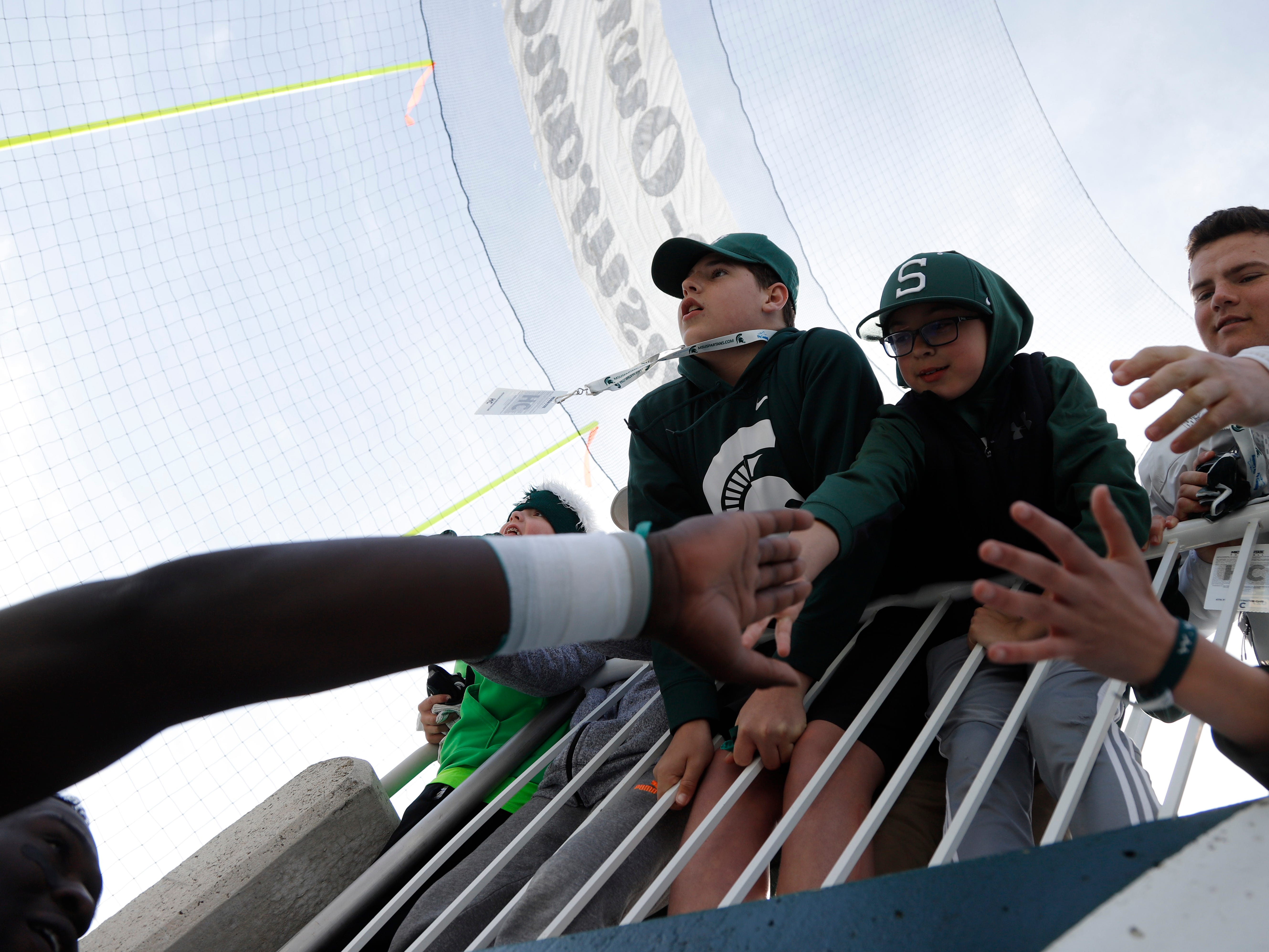 Michigan State's Trenton Gillison, left, greets fans following an NCAA college football spring scrimmage game, Saturday, April 13, 2019, in East Lansing, Mich. (AP Photo/Al Goldis)