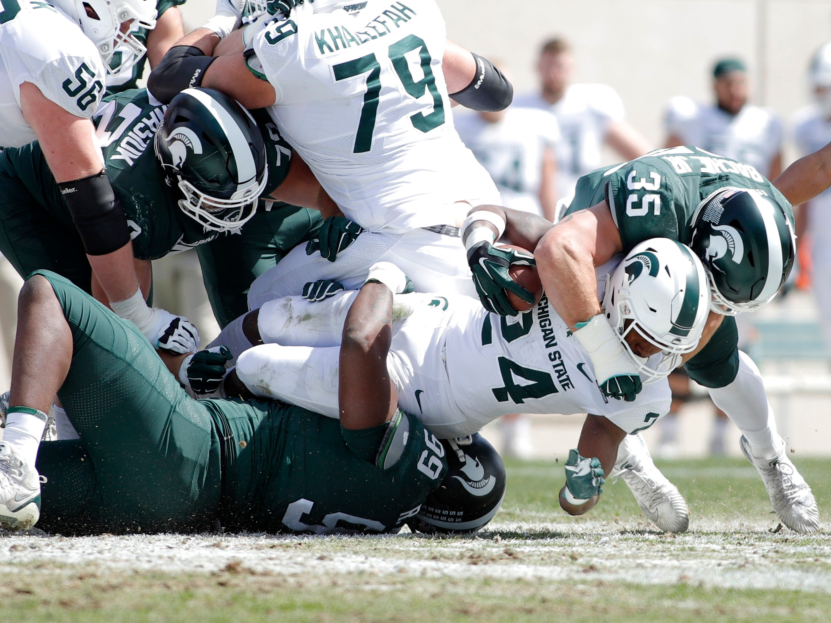 Michigan State's Joe Bachie, right, and Raequan Williams, bottom, tackle Elijah Collins (24) during an NCAA college football spring scrimmage game, Saturday, April 13, 2019, in East Lansing, Mich. (AP Photo/Al Goldis)