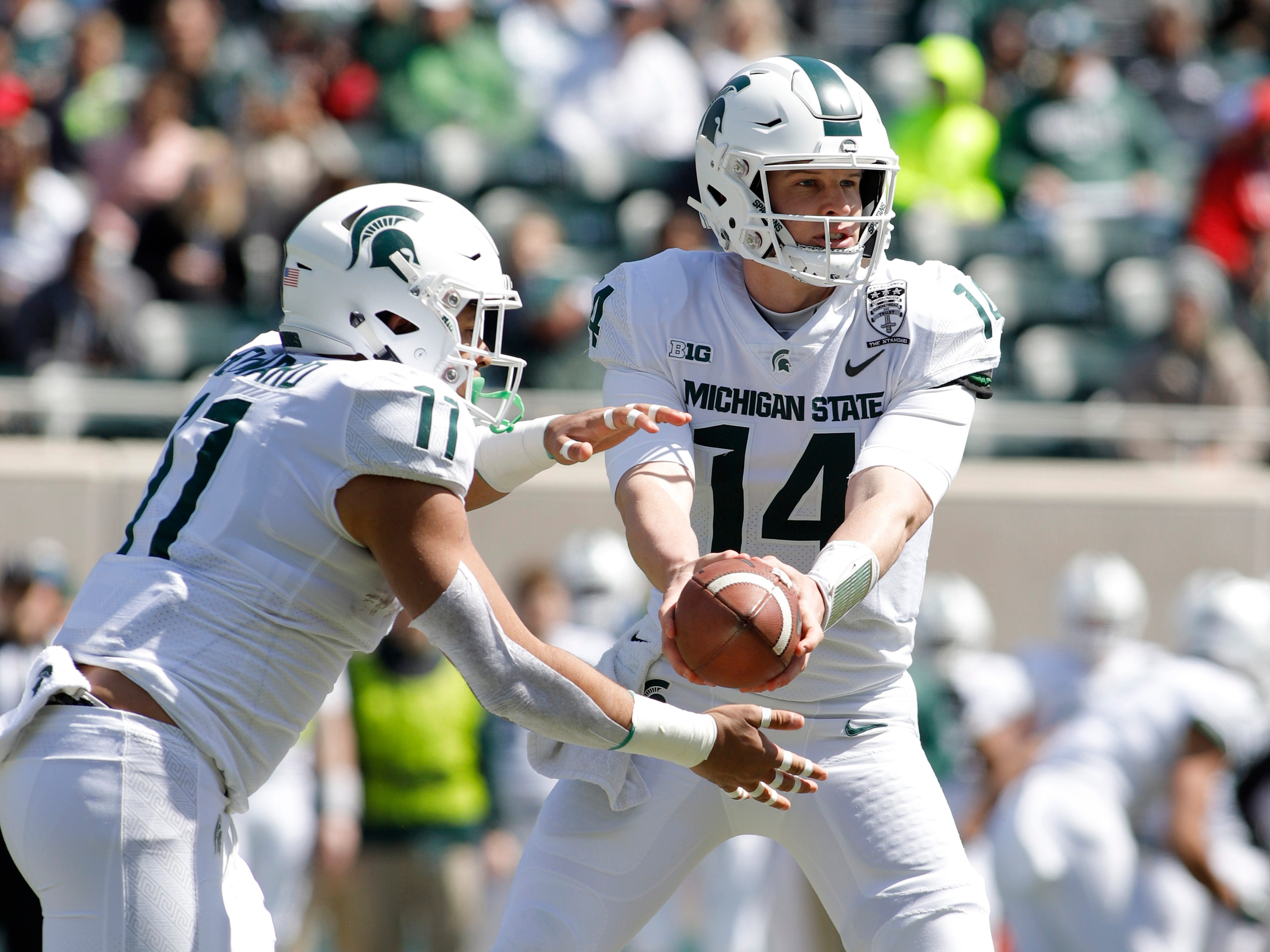 Michigan State quarterback Brian Lewerke, right, hands off to running back Connor Heyward during an NCAA college football spring scrimmage game, Saturday, April 13, 2019, in East Lansing, Mich. (AP Photo/Al Goldis)