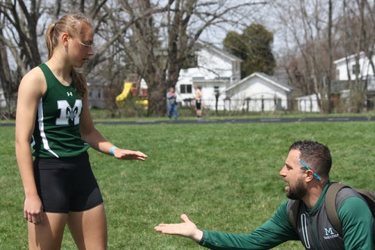 Madison sophomore Taylor Huff gets a congratulatory handshake from coach Andrew Saris during Saturday's 87th Mehock Relays.