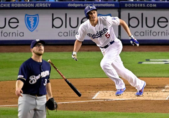 The Dodgers' Corey Seager and Brewers starter Corbin Burnes watch Seager's homer leave the park Friday night in Los Angeles.