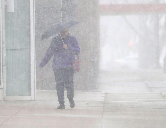 A pedestrian walks through the snow along East Kilbourn Avenue near North Broadway in Milwaukee on April 14.