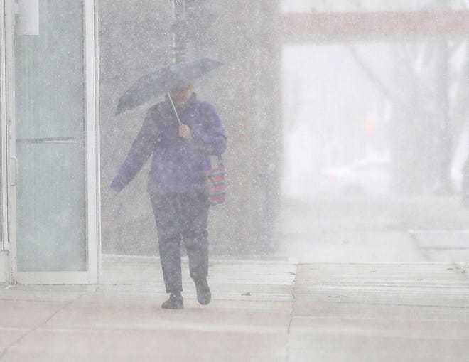 A pedestrian walks through the snow along East Kilbourn Avenue near North Broadway in Milwaukee on April 14.