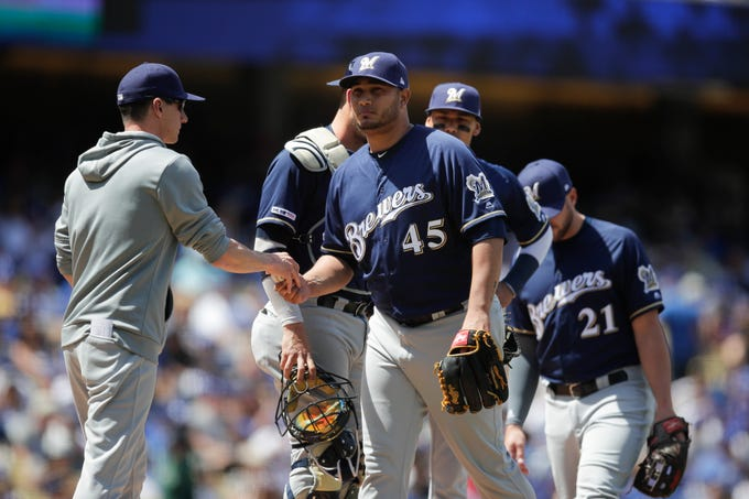 Brewers starting pitcher Jhoulys Chacin gives the ball to manager Craig Counsell after being removed from the game in the third inning.