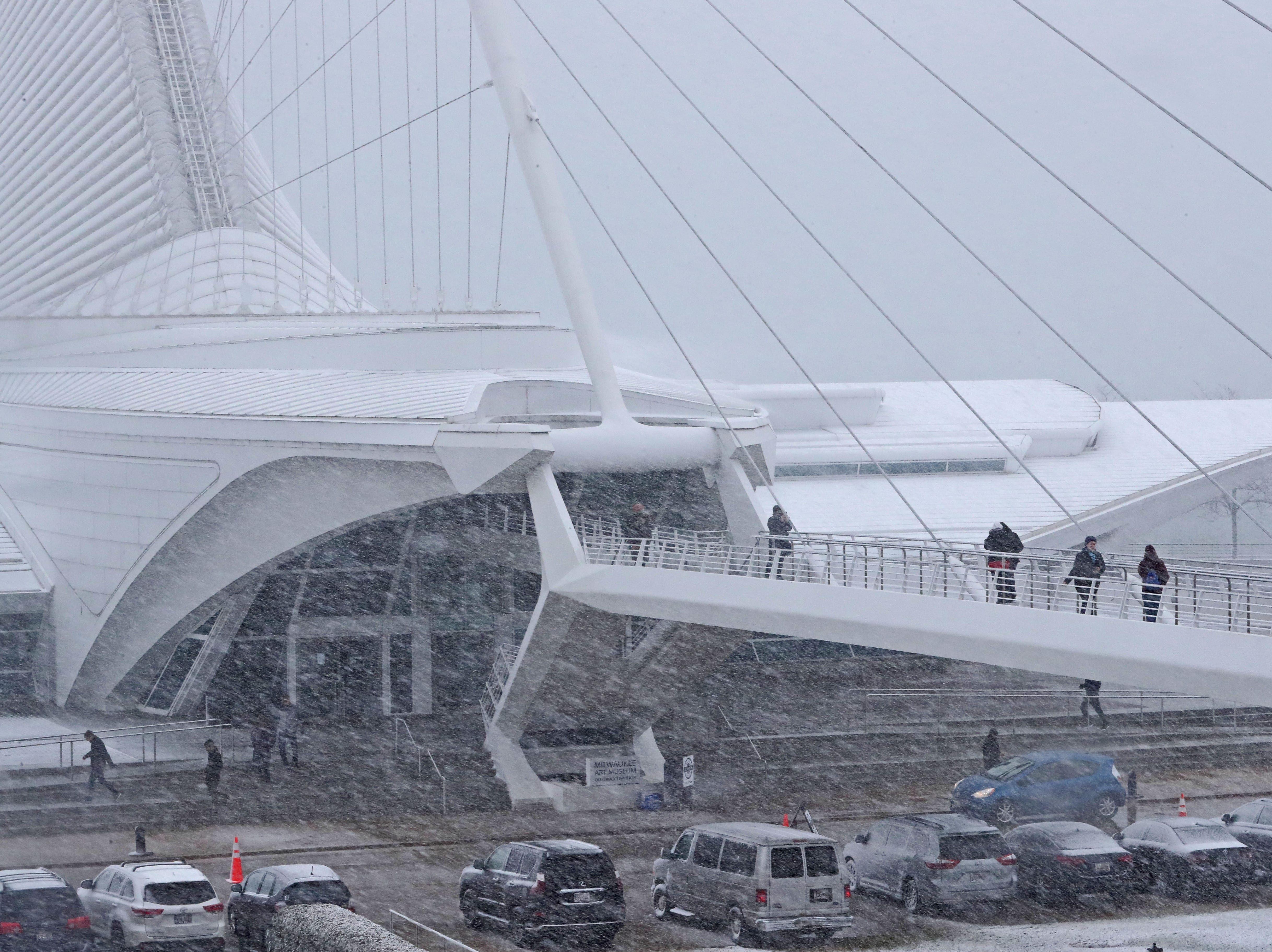 People brave 20 mph winds and heavy wet blowing snow to visit the Milwaukee Art Museum Sunday.