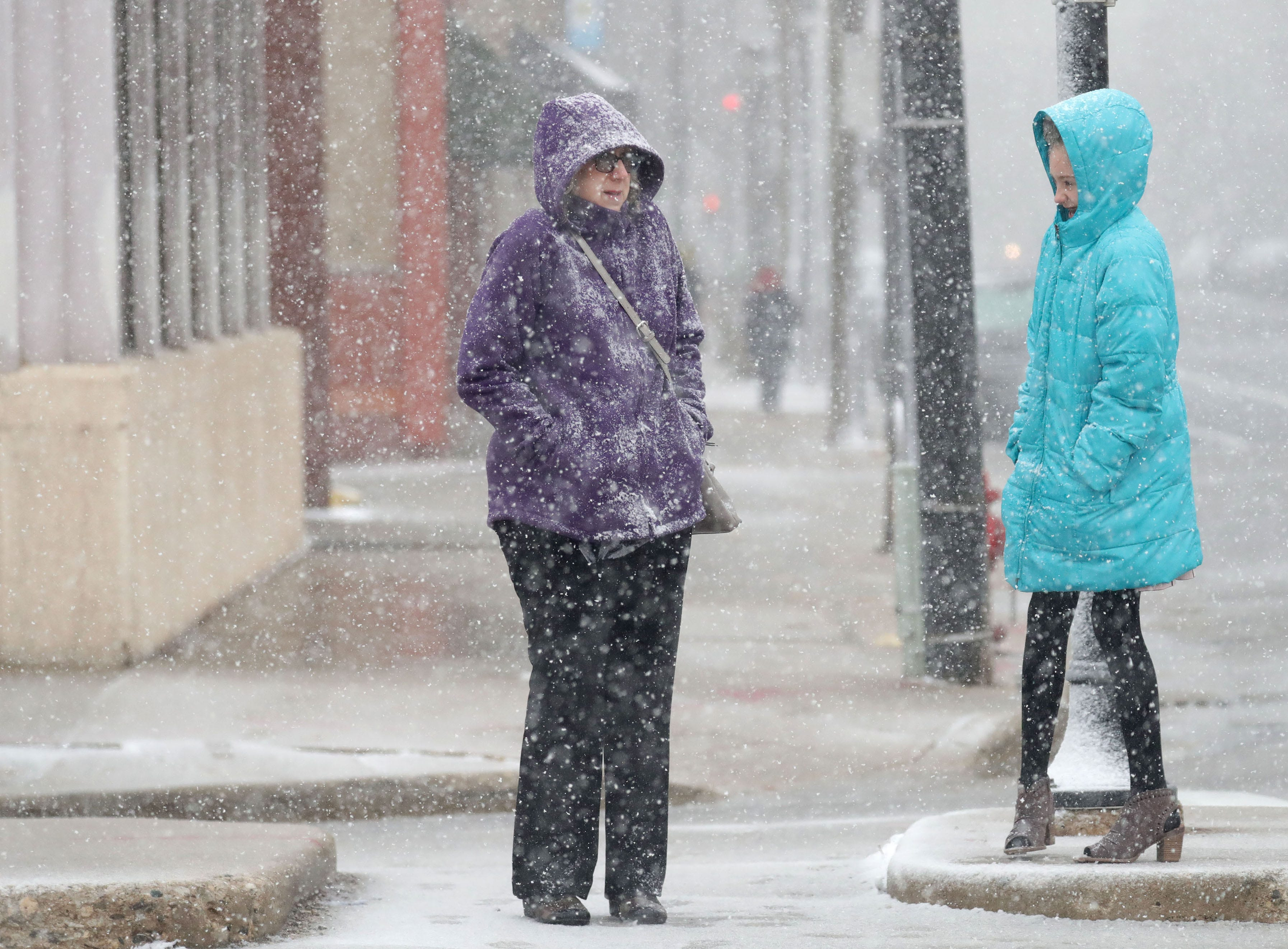 Pedestrians stand in the snow waiting for a light to change on East Kilbourn Avenue and North Plankinton Avenue.