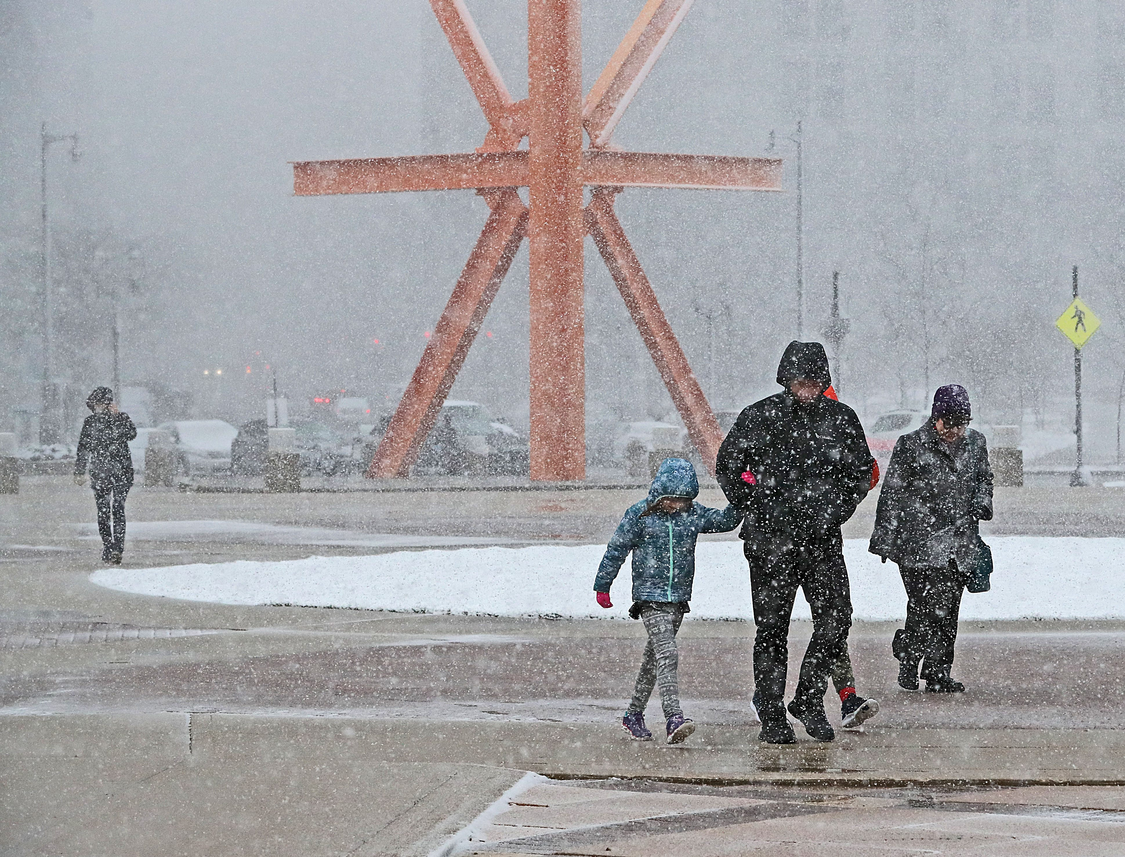 "Gusty winds and wet snow greeted visitors to Milwaukee's lakefront as they walked past the steel sculpture ""The Calling"" by Mark di Suvero located in O'Donnell Park."