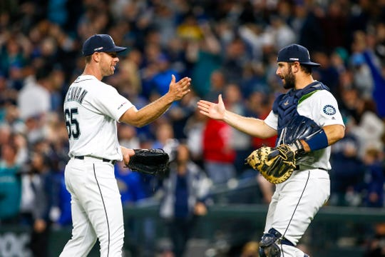 Former Mariners catcher David Freitas (right) greets relief pitcher Brandon Brennan following a 12-4 victory against the Red Sox on March 28.