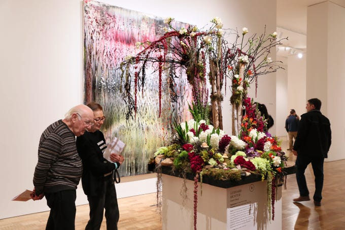 "Roland Dudosq  and his wife, Barbara, of Highland Park, Illinois, look over the floral display by Katie Rush at the Milwaukee Art Museum's ""Art in Bloom"" on Sunday.  Gerhard Richter's work titled ""Breath"" is at rear. The 12th annual event features more than 38 locally crafted floral installations, each inspired by a specific work of art in the museum's collection."