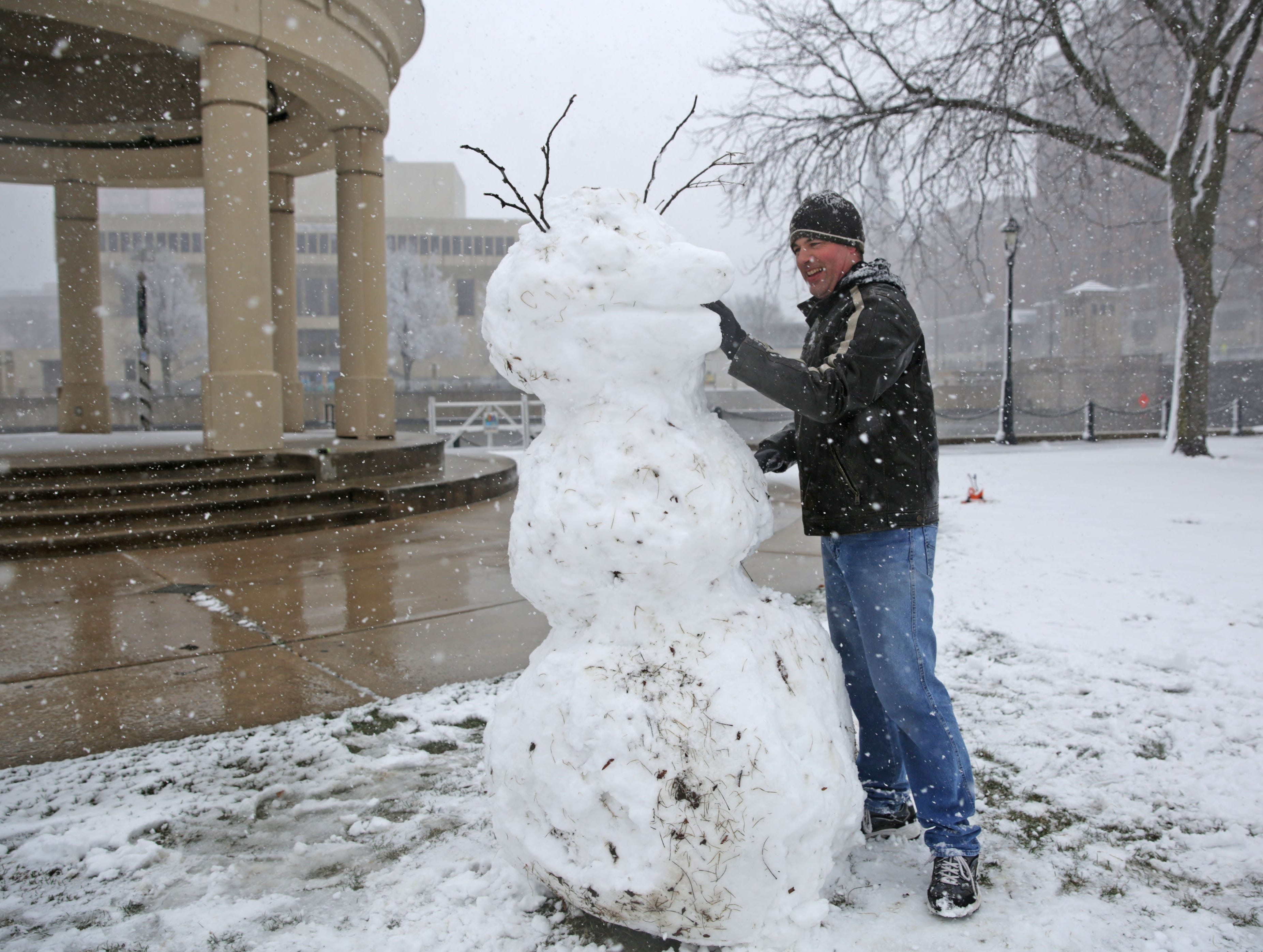 Jody Wyskochil of Milwaukee takes advantage of the spring snowfall Sunday as he builds a snowman at Pere Marquette Park resembling a buck to support the Milwaukee Bucks in the NBA playoffs in Milwaukee.