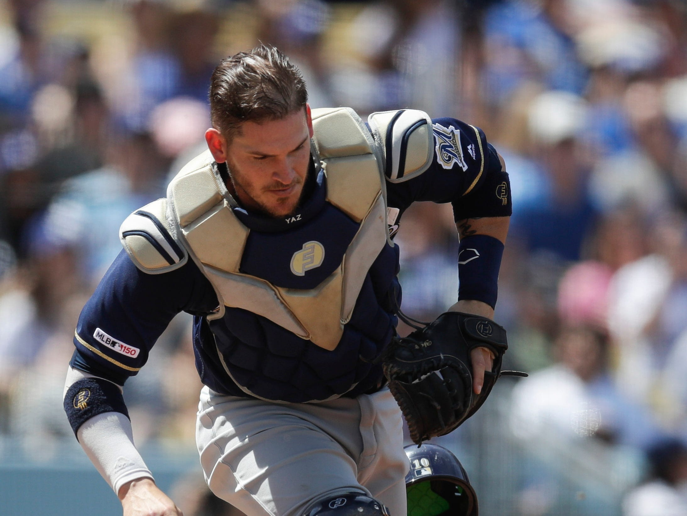 Brewers catcher Yasmani Grandal chases a foul ball.