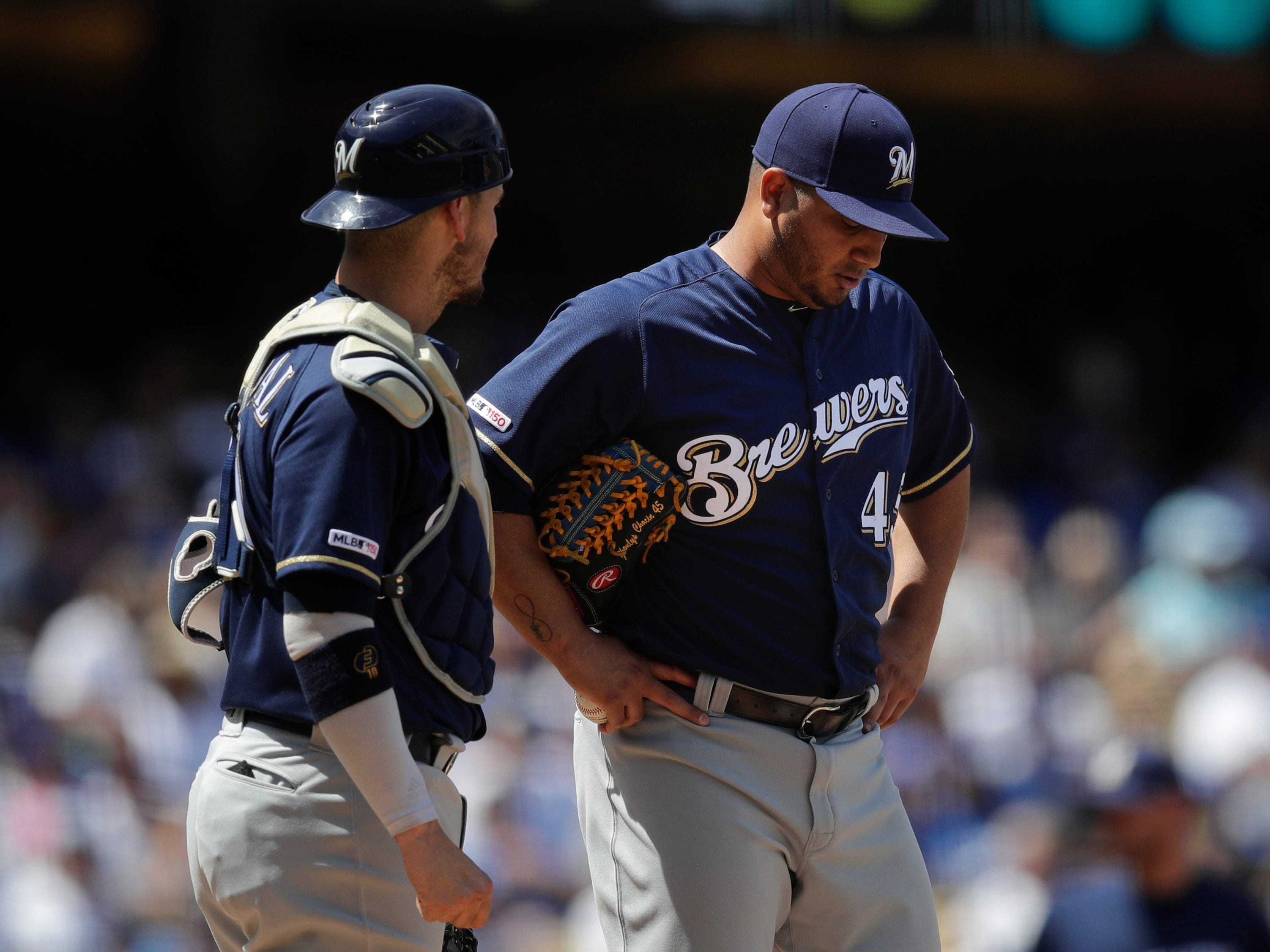 Brewers catcher Yasmani Grandal (left), talks to starting pitcher Jhoulys Chacin during the third inning.