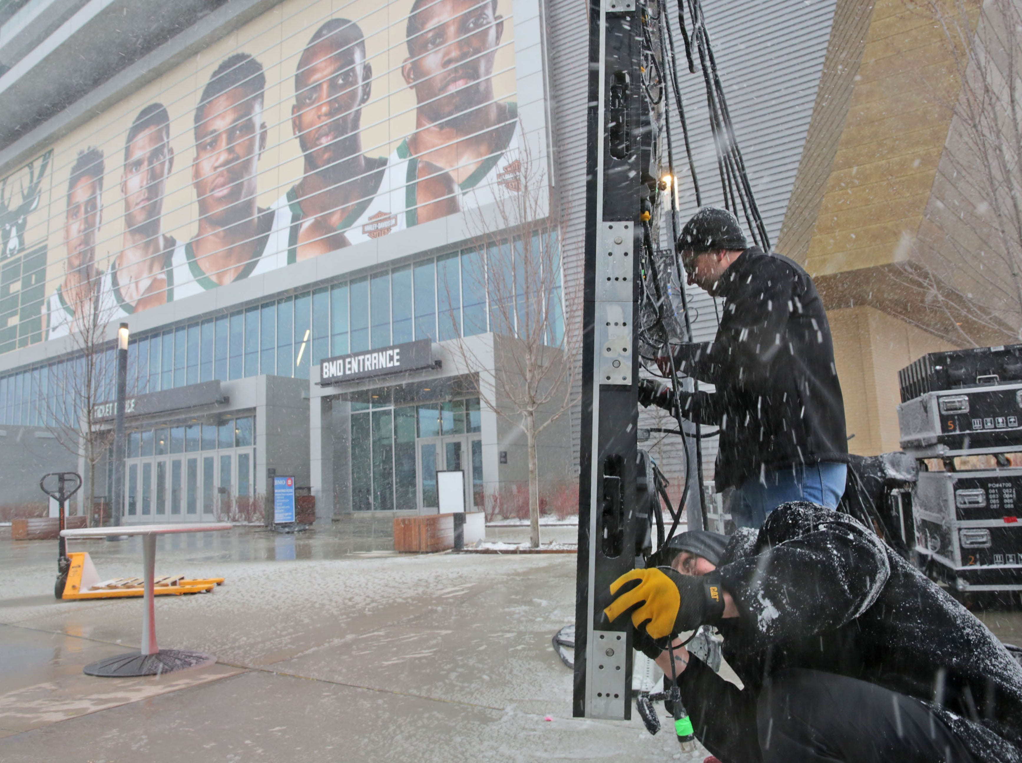 Paul Makowski (above) and Gunther Rosentreter of Exciting Events work in the snow to hook up an outdoor video board at Fiserv Forum before game one in the first round of the NBA playoffs at Fiserv Forum.