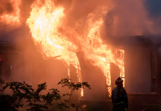 A lone firefighter watches as flames shoot out of the windows of Boley Elementary in West Monroe, La. on April 13. Firefighters were unable to contain the fire before it spread to other parts of the building when they initially responded about 5 p.m. and as of 8 p.m. the fire was still not under control. The cause of the fire is yet to be determined.