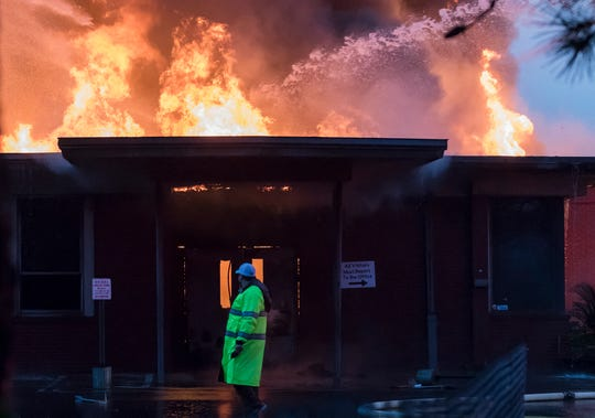 A firefighter walks past an entryway to Boley Elementary in West Monroe, La. as flames emanate from the roof on April 13. Firefighters were unable to contain the fire before it spread to other parts of the building when they initially responded about 5 p.m. and as of 8 p.m. the fire was still not under control. The cause of the fire is yet to be determined.