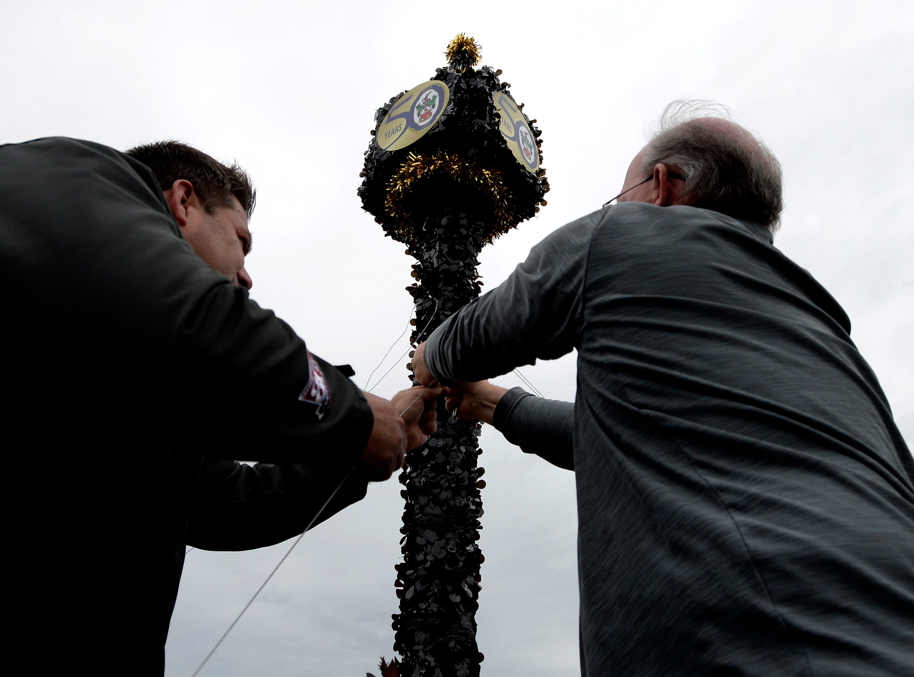 """Glenn Allison, left, and Steve Lugwig adjust wires to Brentwood Morning Rotary float before the start of Brentwood's """"A Golden Gallop"""" parade celebrating its 50th year as a community on Saturday, April 13, 2019, in Brentwood, Tenn."""