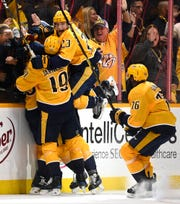 Nashville Predators center Rocco Grimaldi (23) jumps on right wing Craig Smith (15) and center Calle Jarnkrok (19) as defenseman P.K. Subban (76) joins in after Smith scored the game-winning shot during overtime of the Predators' 2-1 win in the divisional semifinal game at Bridgestone Arena in Nashville, Tenn., Saturday, April 13, 2019.