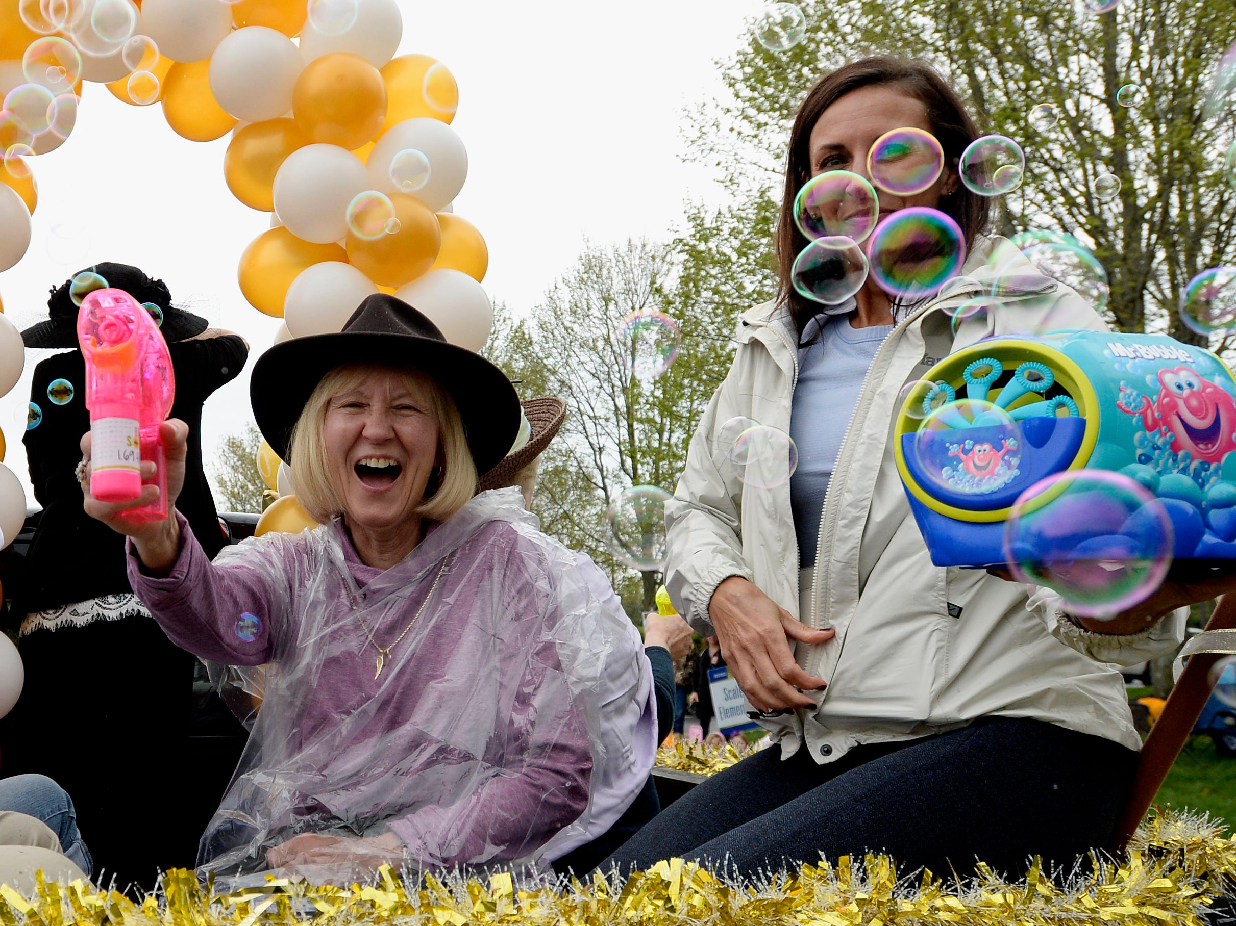 """Participants blow bubbles as they ride on a float during Brentwood's """"A Golden Gallop"""" parade celebrating its 50th year as a community on Saturday, April 13, 2019, in Brentwood, Tenn."""