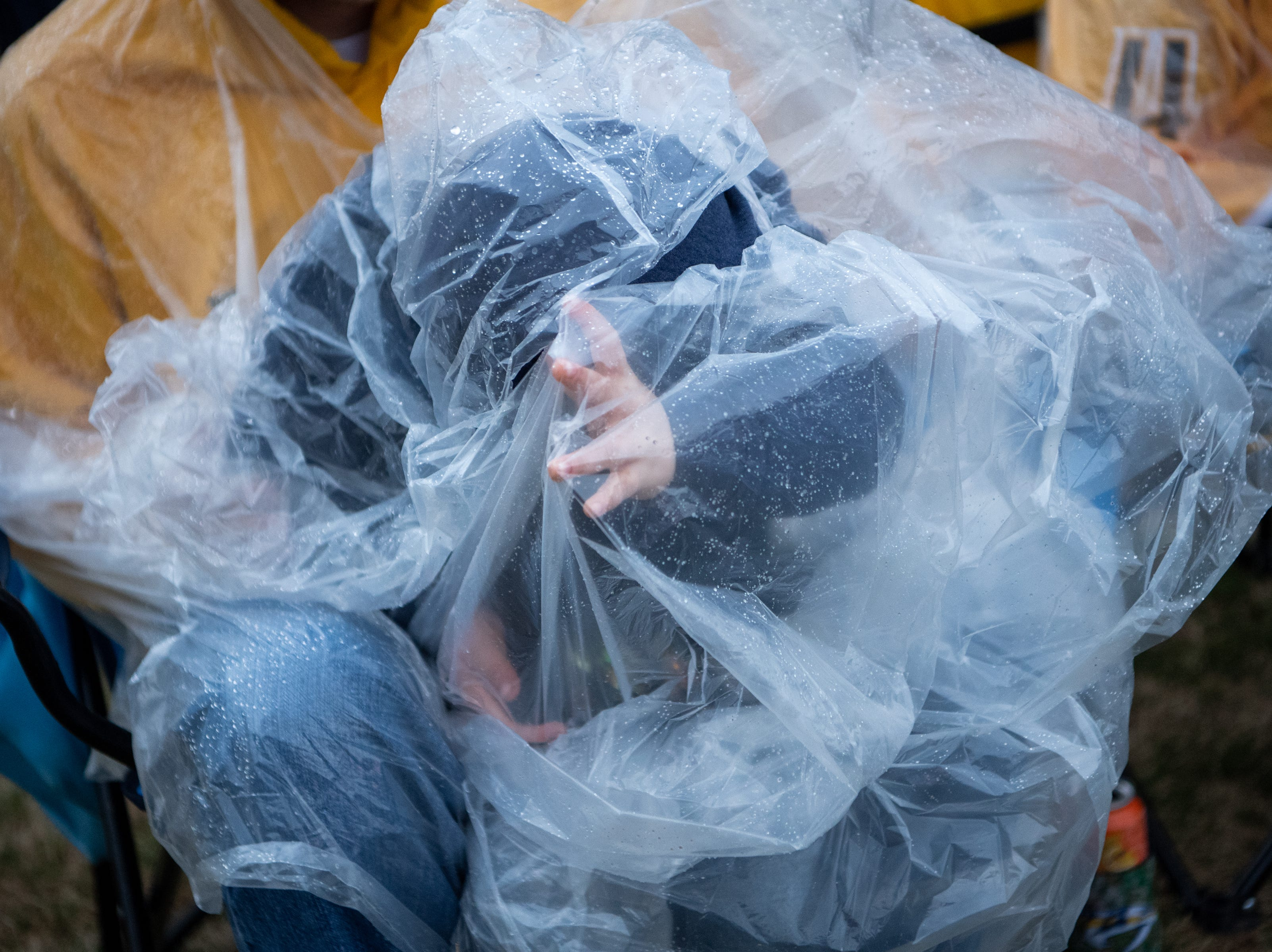 JD Conrey, 4, struggles under a rain poncho during the second period of the Nashville Predators game against the Dallas Stars at Preds Party in the Park at Walk of Fame Park Saturday, April 13, 2019, in Nashville, Tenn.