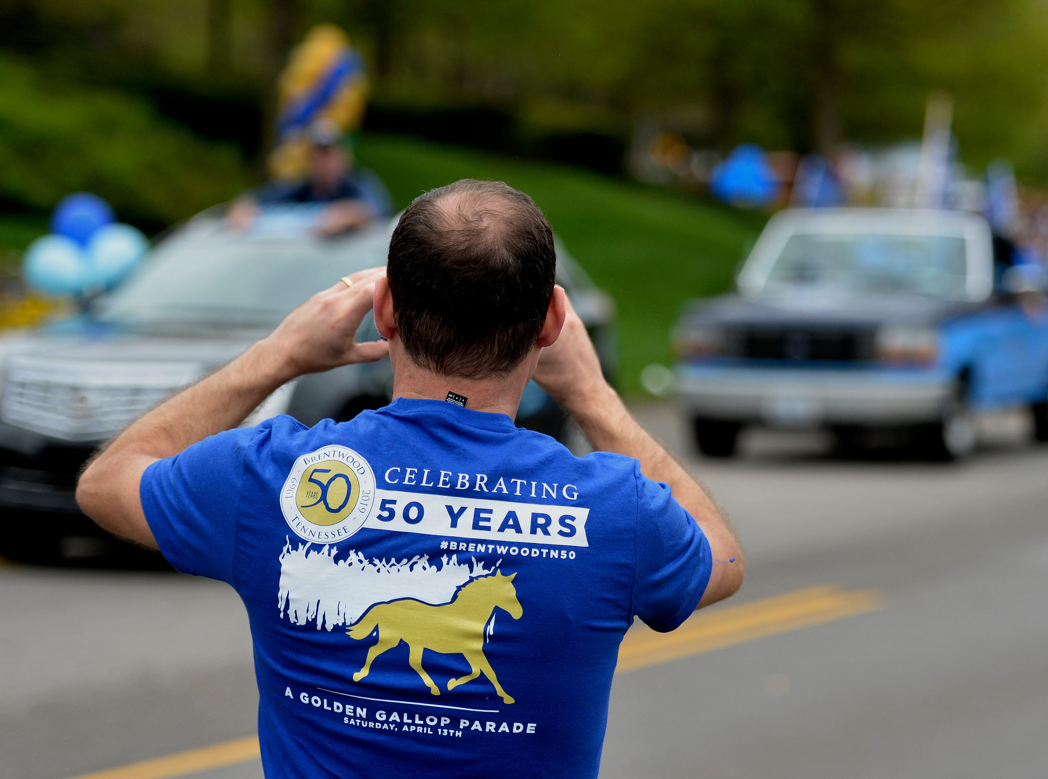 """A man takes photographs during Brentwood's """"A Golden Gallop"""" parade celebrating its 50th year as a community on Saturday, April 13, 2019, in Brentwood, Tenn."""