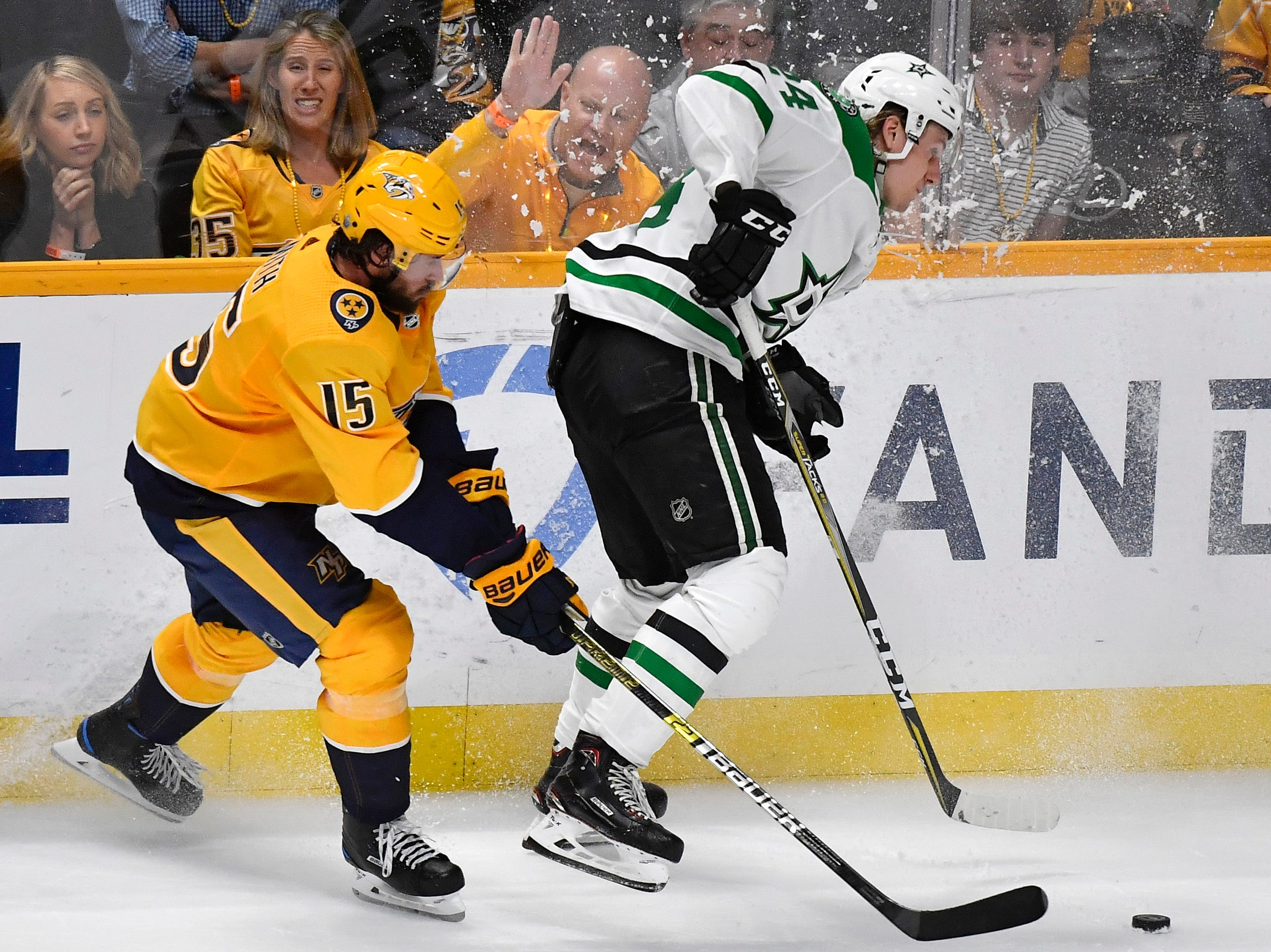 Nashville Predators right wing Craig Smith (15) and Dallas Stars left wing Roope Hintz (24) battle along the boards during the third period of the divisional semifinal game at Bridgestone Arena in Nashville, Tenn., Saturday, April 13, 2019.