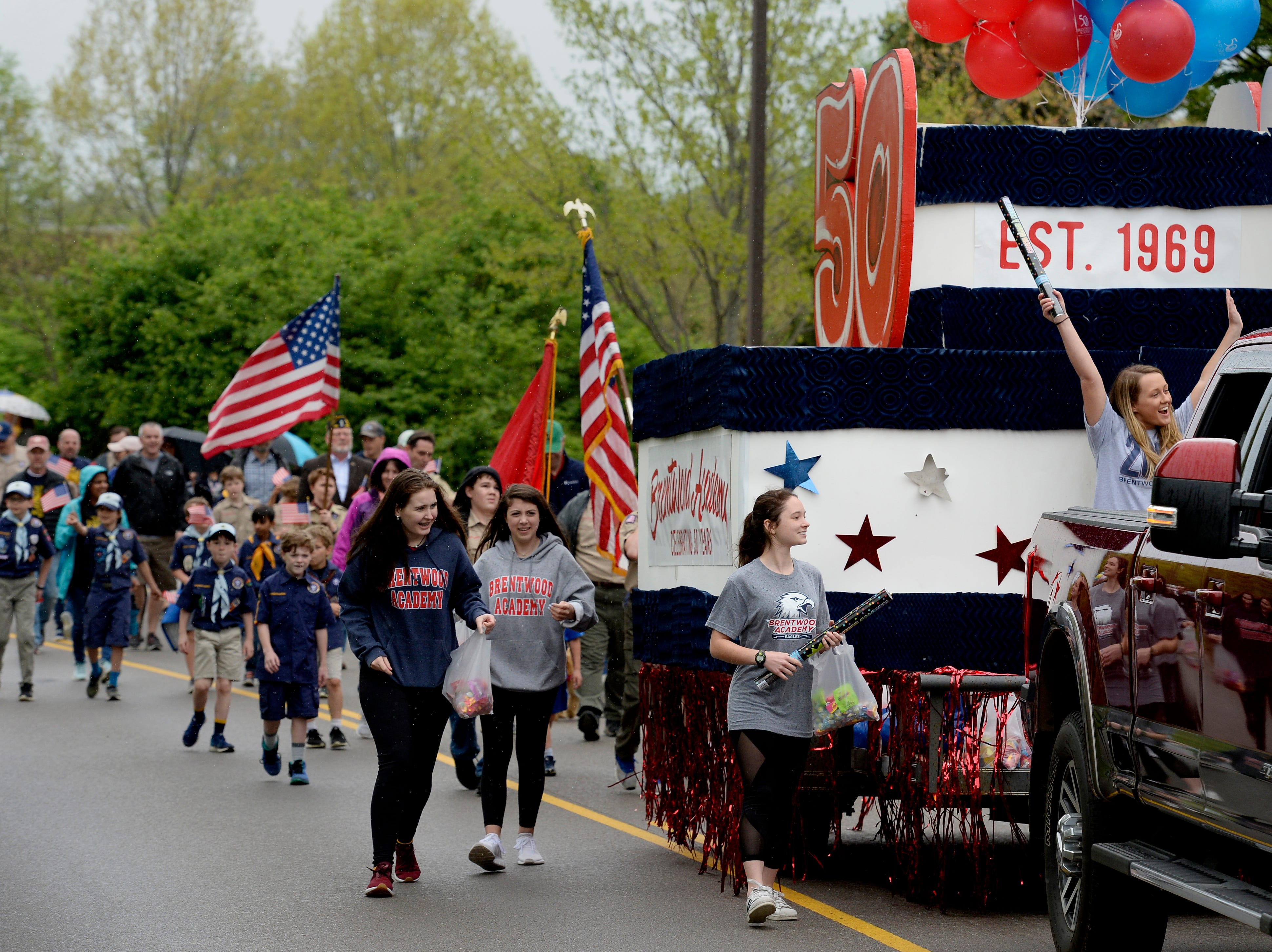 """People walk and cheer as they participate in Brentwood's """"A Golden Gallop"""" parade celebrating its 50th year as a community on Saturday, April 13, 2019, in Brentwood, Tenn."""