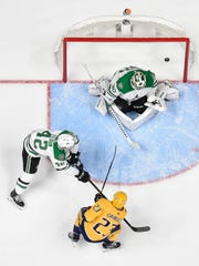 The Predators' Rocco Grimaldi scores his first career playoff goal, beating Stars goaltender Ben Bishop in Nashville's 2-1 overtime win Saturday at Bridgestone Arena.