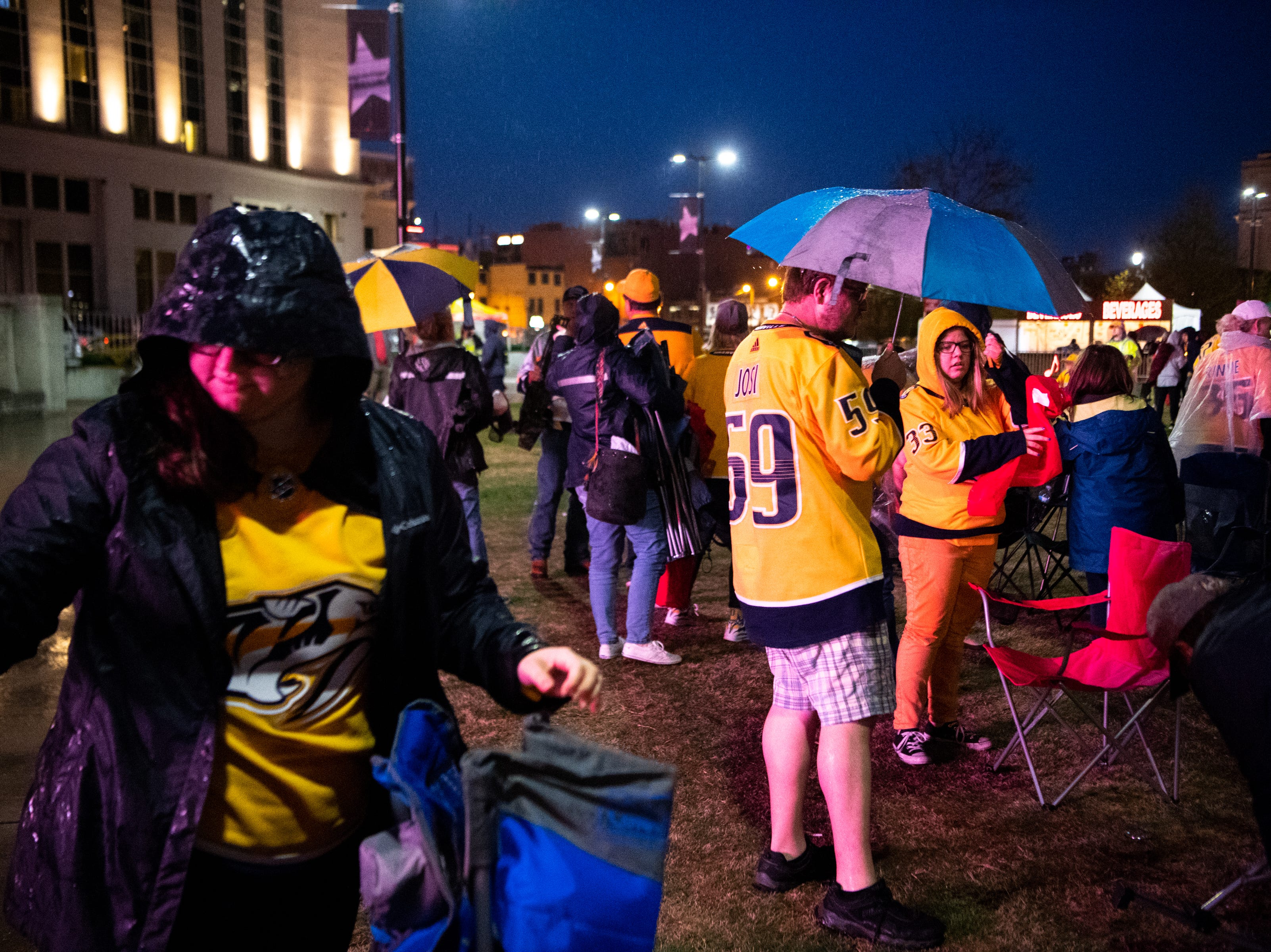People pack up their belongings after a severe weather warning caused the cancelation of Preds Party in the Park at Walk of Fame Park during the third period of the Nashville Predators game against the Dallas Stars  Saturday, April 13, 2019, in Nashville, Tenn.