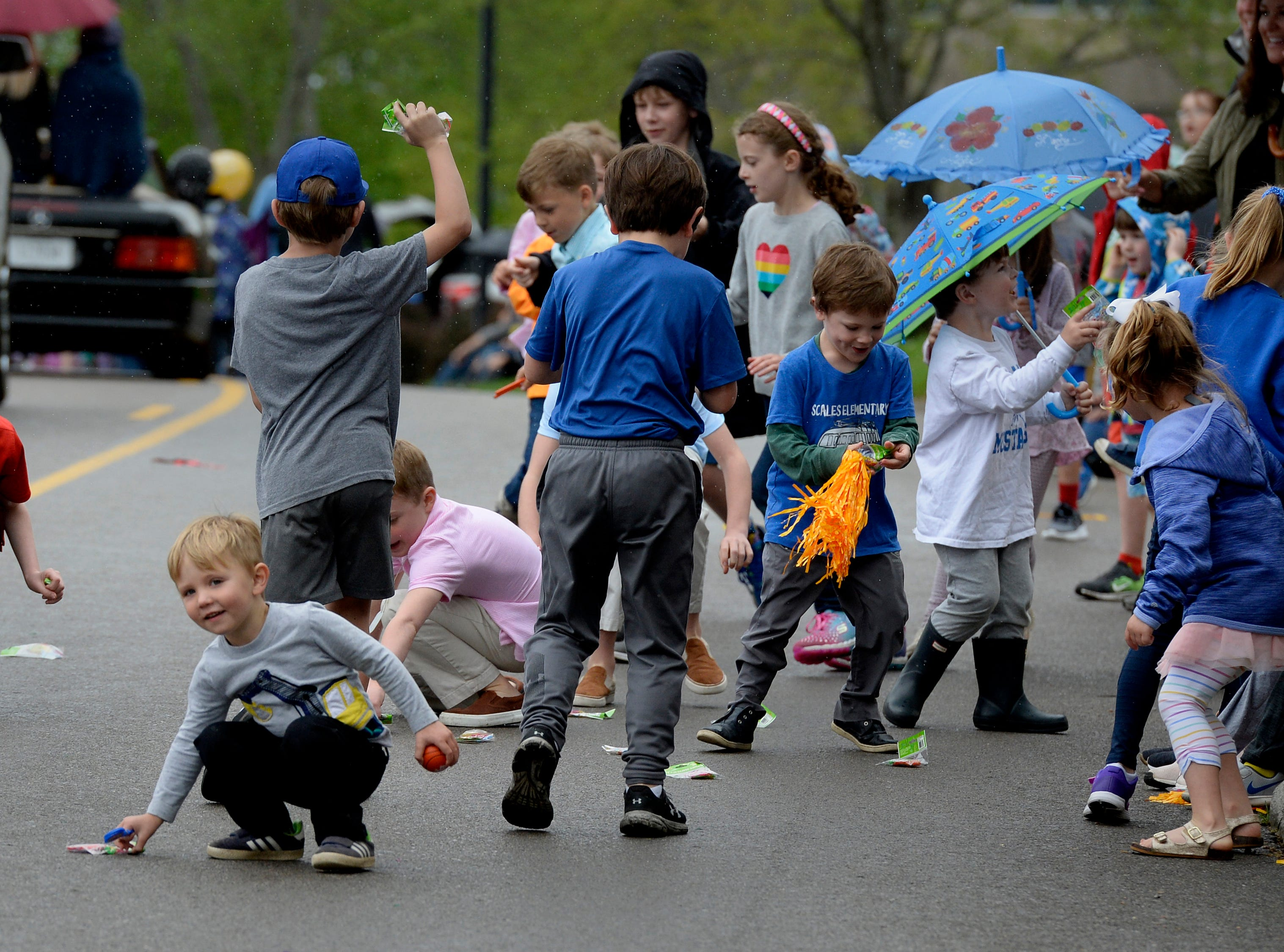 """Children scramble to gather up candy along the parade route during Brentwood's """"A Golden Gallop"""" parade celebrating its 50th year as a community on Saturday, April 13, 2019, in Brentwood, Tenn."""
