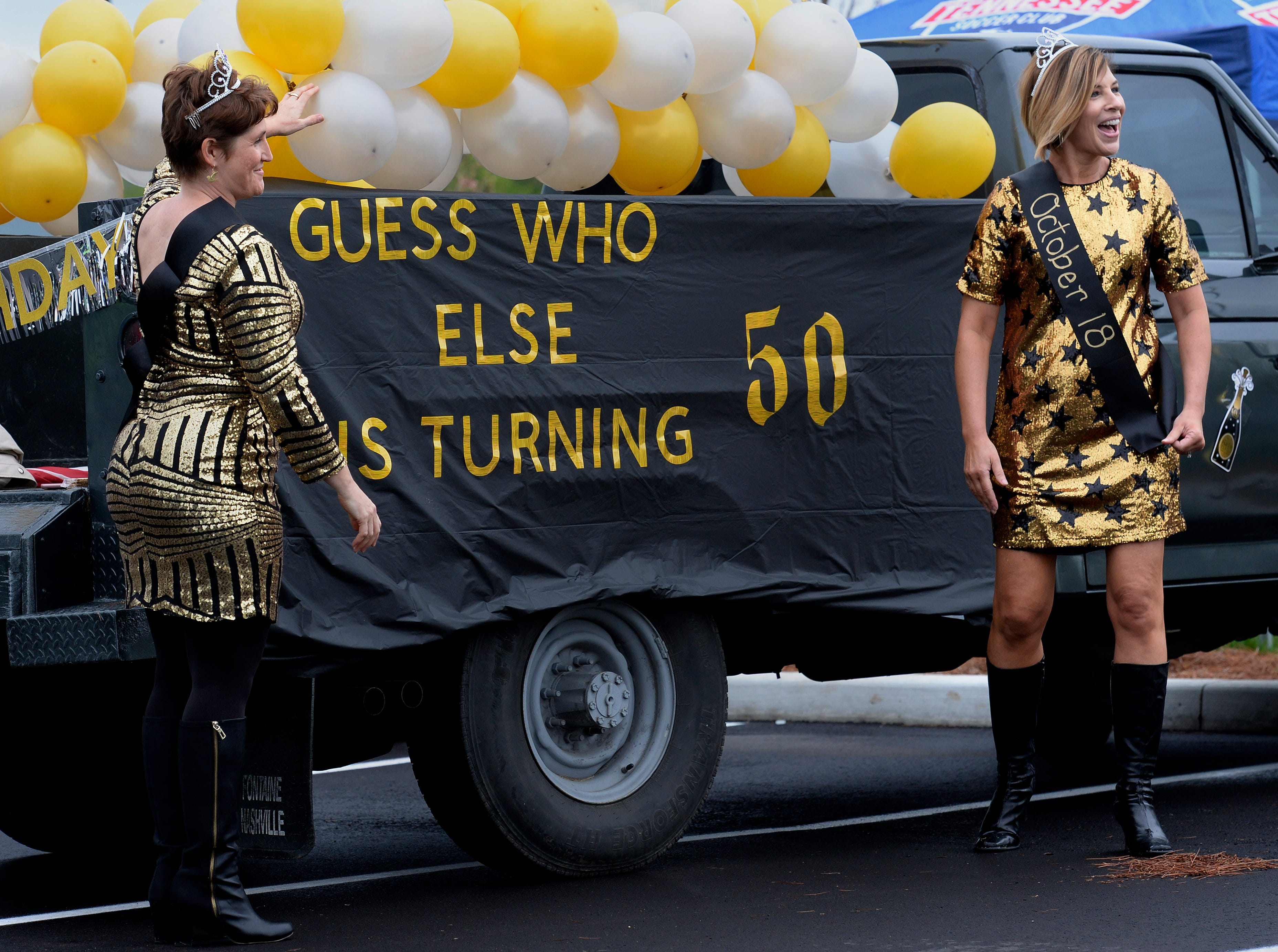 """Stacy Elliott, left, and Melissa Oliver stand by the float they will riding on before the start of Brentwood's """"A Golden Gallop"""" parade celebrating its 50th year as a community on Saturday, April 13, 2019, in Brentwood, Tenn."""