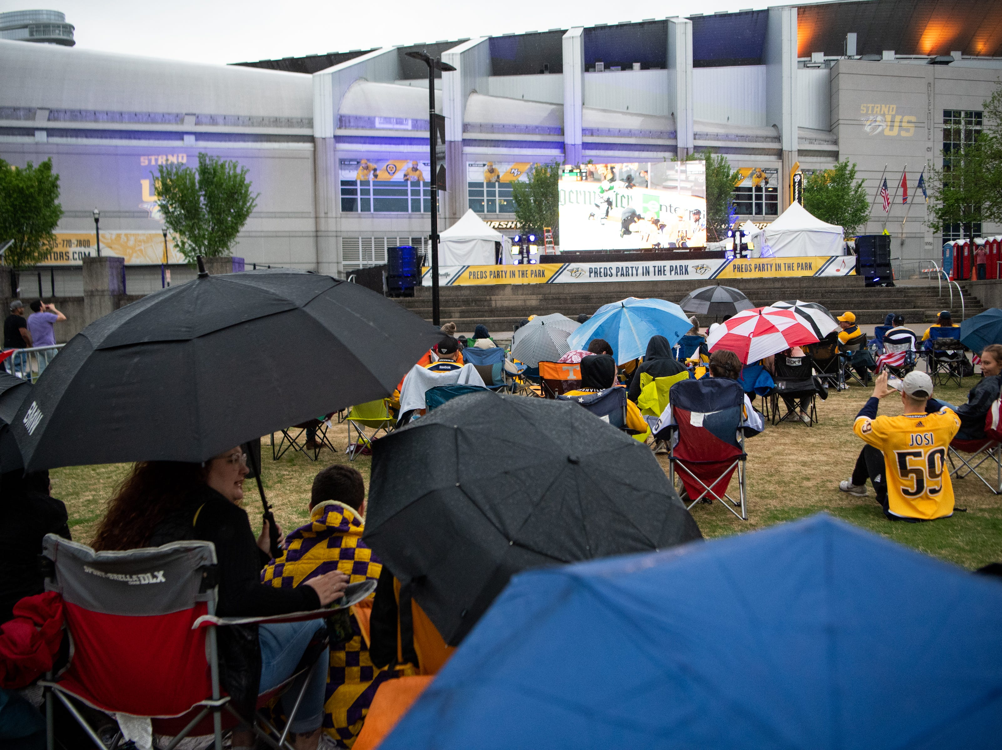 Fans try to stay warm and dry during the second period of the Nashville Predators game against the Dallas Stars at Preds Party in the Park at Walk of Fame Park Saturday, April 13, 2019, in Nashville, Tenn.